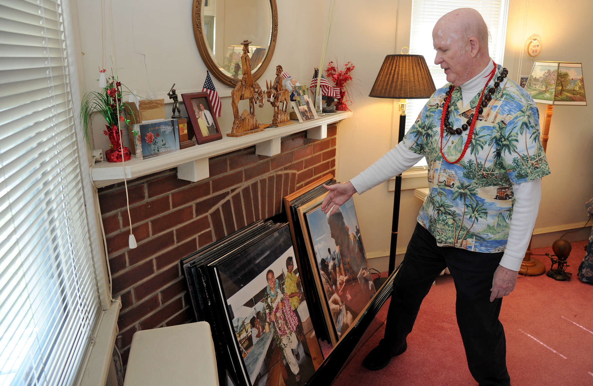 In the living room of his home in Audubon, Craig E. Burgess, a retired Cherry Hill East teacher, looks through photos from his many visits to Hawaii.