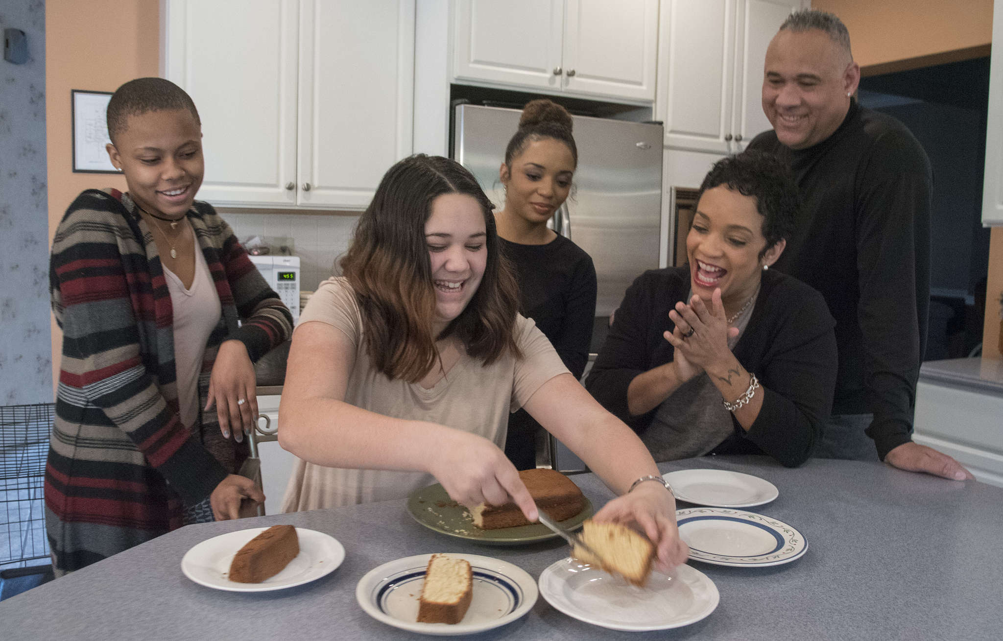 Audelia Crabbe cuts her cake on her 14th birthday with her adoptive family (from left) Nacera Wynn, Billie Walker, Valerie Crabbe and Larry Harris.