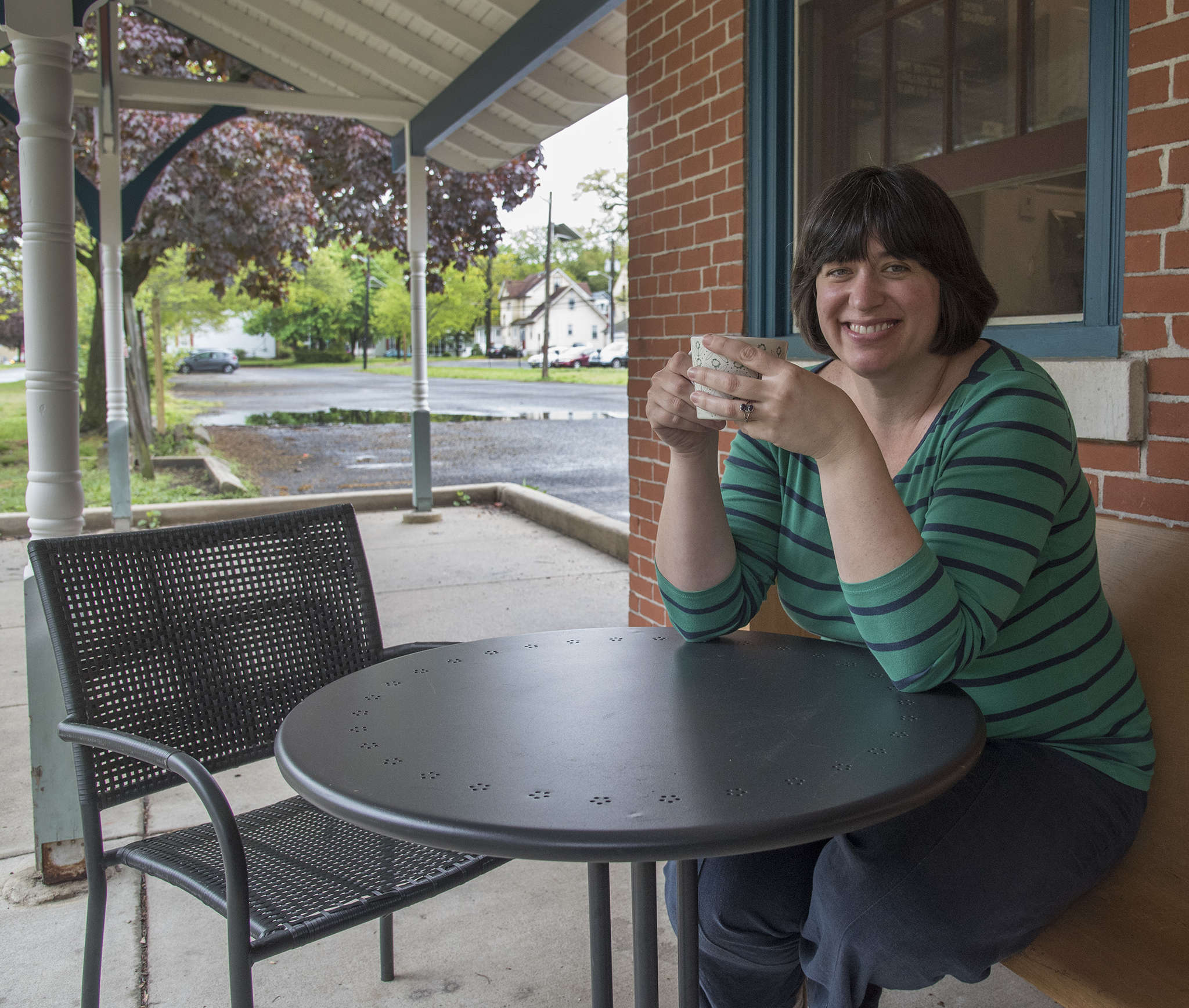 "Councilwoman Katherine Swann sits outside her coffee shop, with the lot in view.""I have faith in what´s happening in town,"" she says."