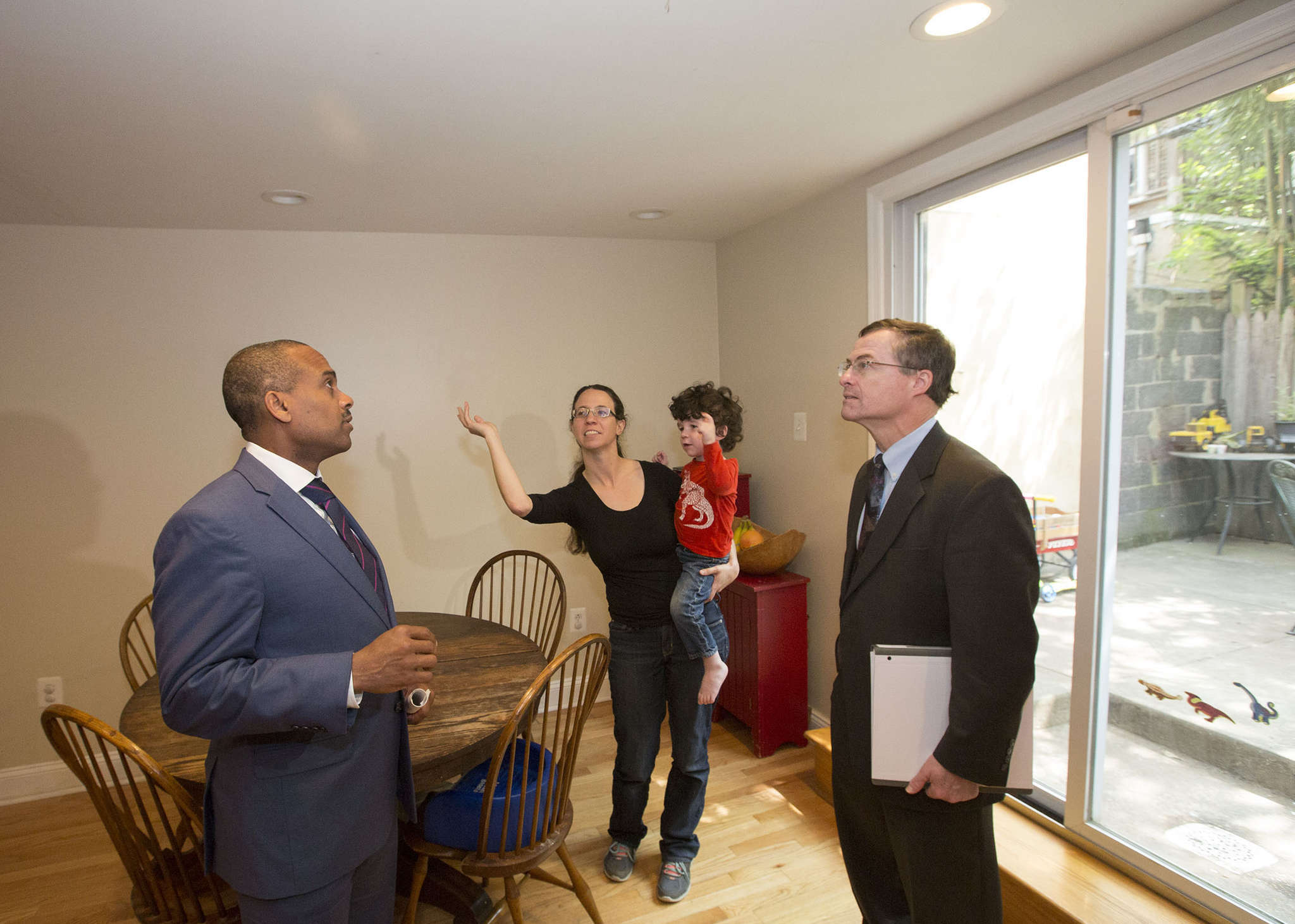 Lizzie Rothwell shows state Treasury Secretary Timothy Reese (left) and DEP Secretary John Quigley around her South Philadelphia home. She used the KeystoneHelp loan program to make it more energy efficient.