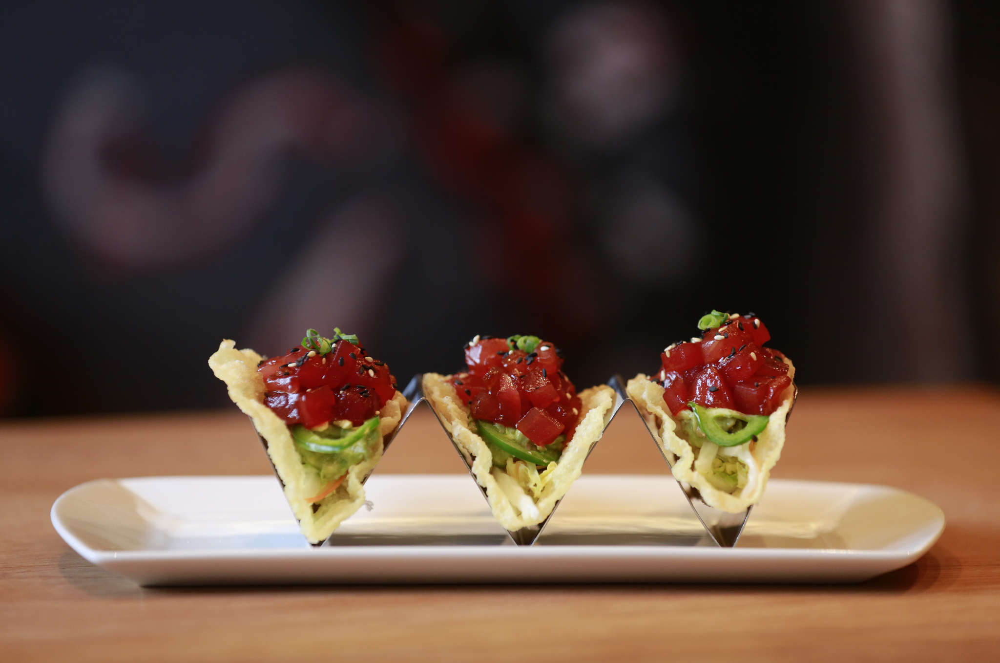 Crispy tacos at SUGA, their shells made from fried wonton skins, are topped with diced sushi tuna.