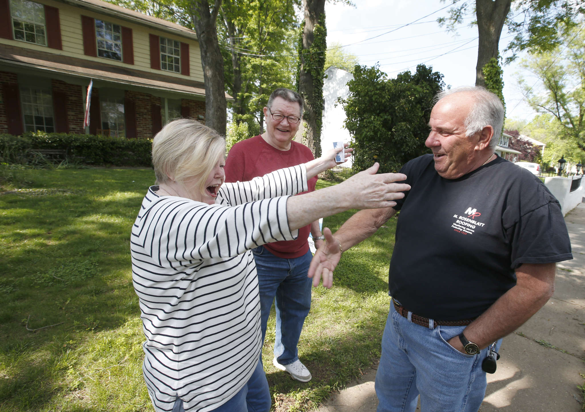 Stephen Meller, third-generation owner of M. Rosenblatt Roofing & Siding, reaches to shake the hand of Pat Porter. She, on the other hand, wants to give him a hug. His firm will donate the labor, another source will finance the materials.