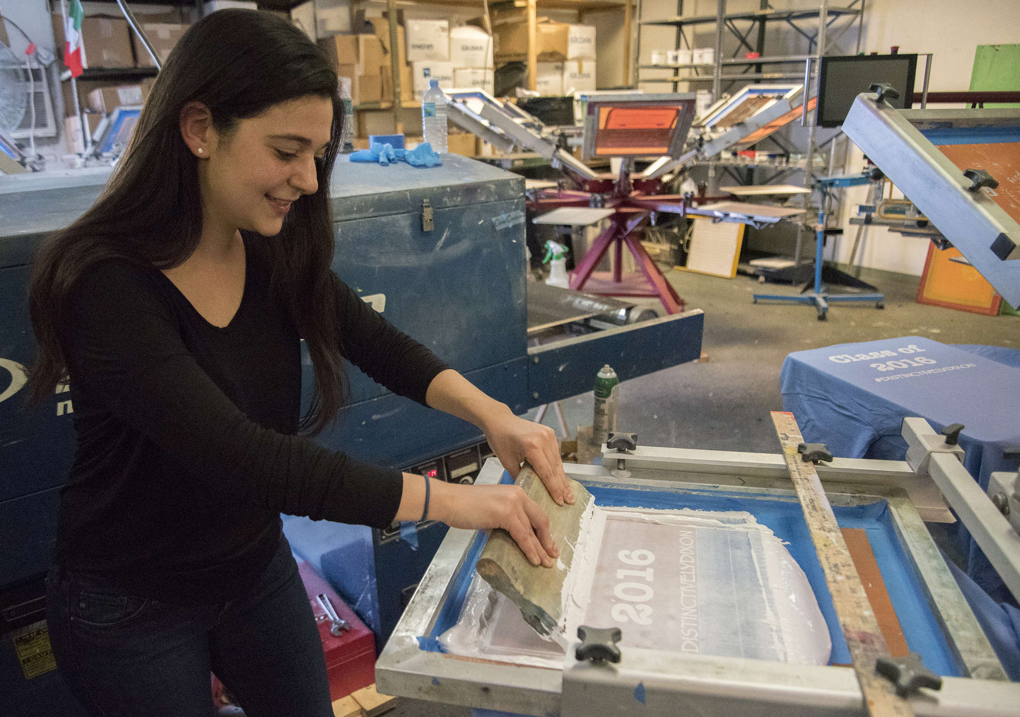 Melanie Weinsten, a Penn campus manager for Fresh Prints, uses a screen printer at Tee Vision Printing.