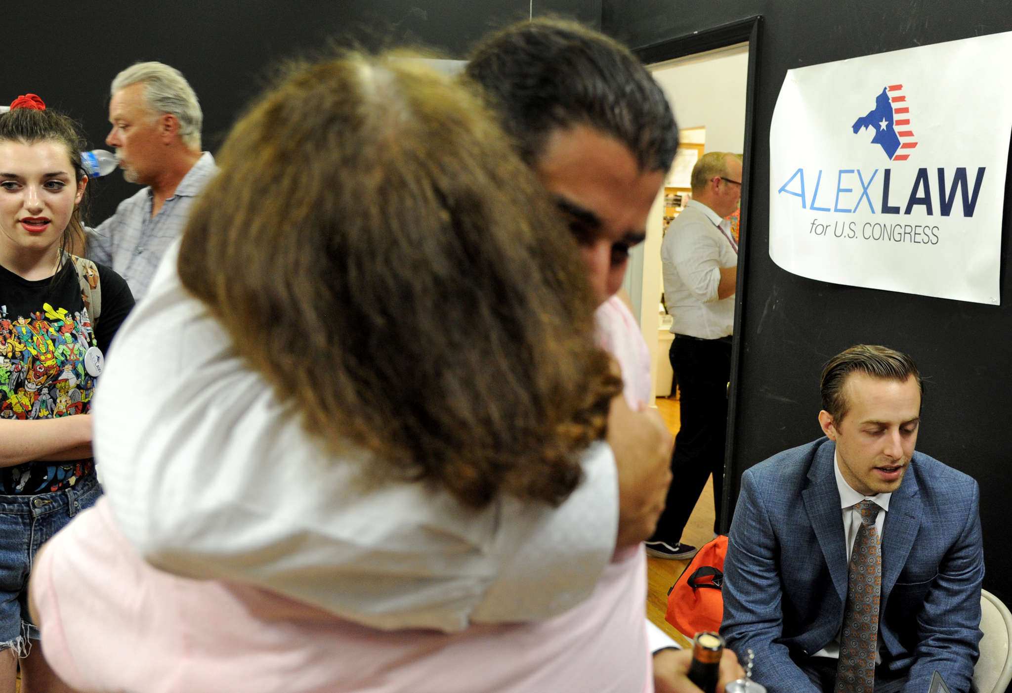 Alex Law (right) talks to a reporter in his Haddon Township campaign headquarters, surrounded by supporters, after his loss to Donald Norcross in a Democratic congressional primary.