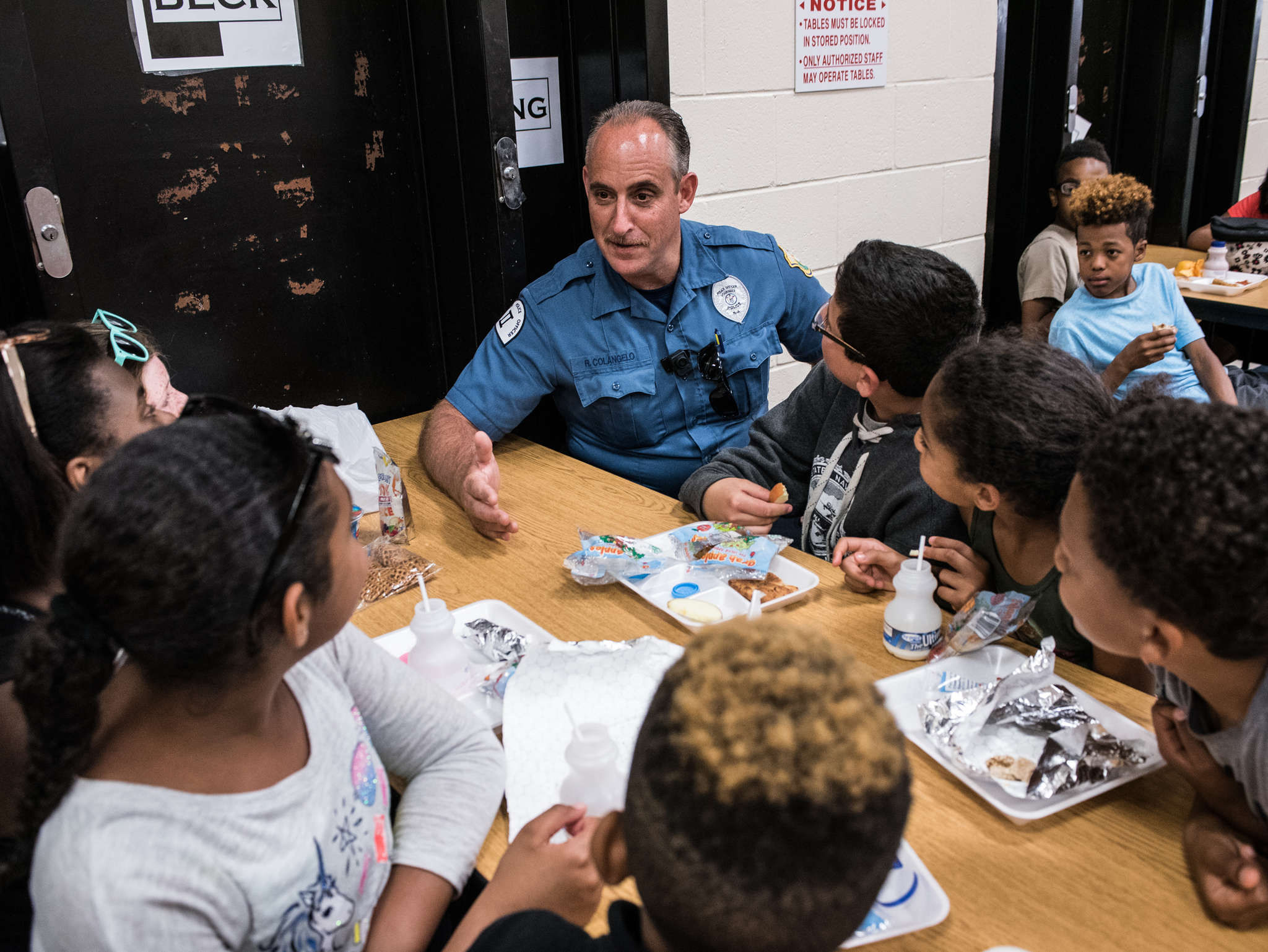 "Colangelo talks with students during lunch. Experienced at community policing, he tries to positively interact throughout the day. ""Officer Bob is kind. He´s cool,"" a sixth grader says. "". . . He has my back and I have his back."""