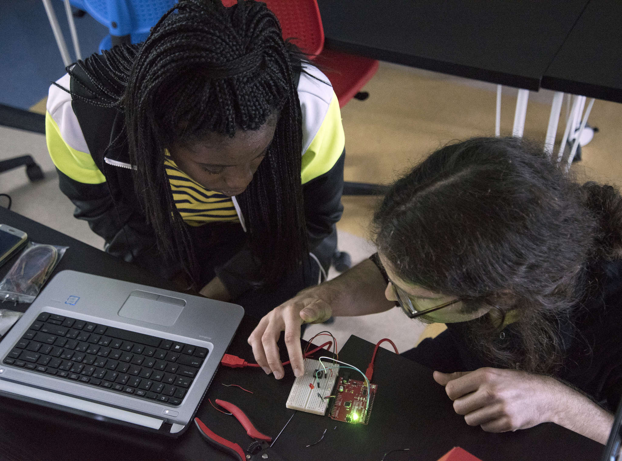 "At Roxborough High School, Onyea Cropper, 16, and her instructor Jeff Gregorio work on a ""breadboard"" using Arduino software."