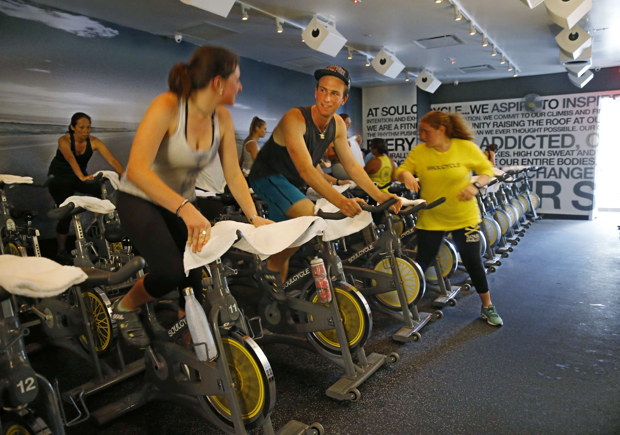 At the SoulCycle in Ardmore, friends Grace Weiner and Seth Caplan chat as they warm up before a class. The studio is the first SoulCycle in Pennsylvania.
