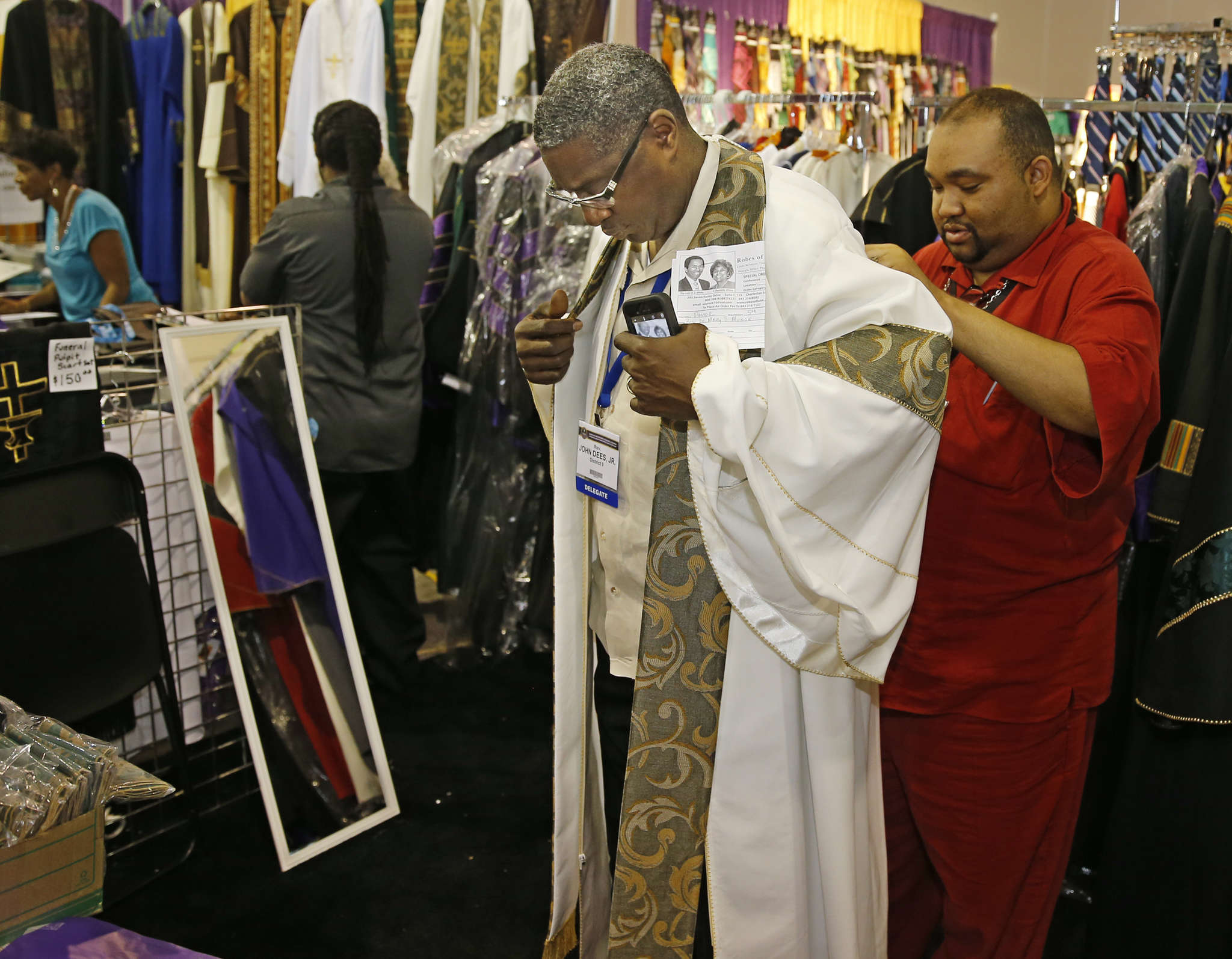 The Rev. John L. Dees Jr. from Mobile, Ala., tries on a preacher´s First Sunday robe with the help of the Rev. Willis Camp III at a booth in the expo hall of the Convention Center. The African Methodist Episcopal conference gathered faithful from all over the country and the world. MICHAEL BRYANT / Staff photographer