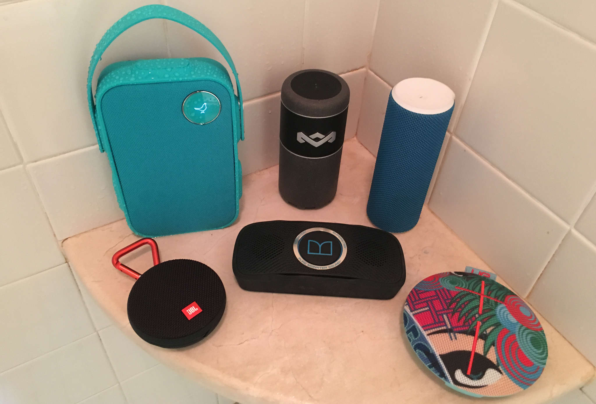 Wet and wild, water shrugging Bluetooth speakers include (back row, left) Libratone One, House of Marley Chant Sport, UE Boom, (front row, left) JBL Clip 2, Monster Superstar, and UE Roll 2.