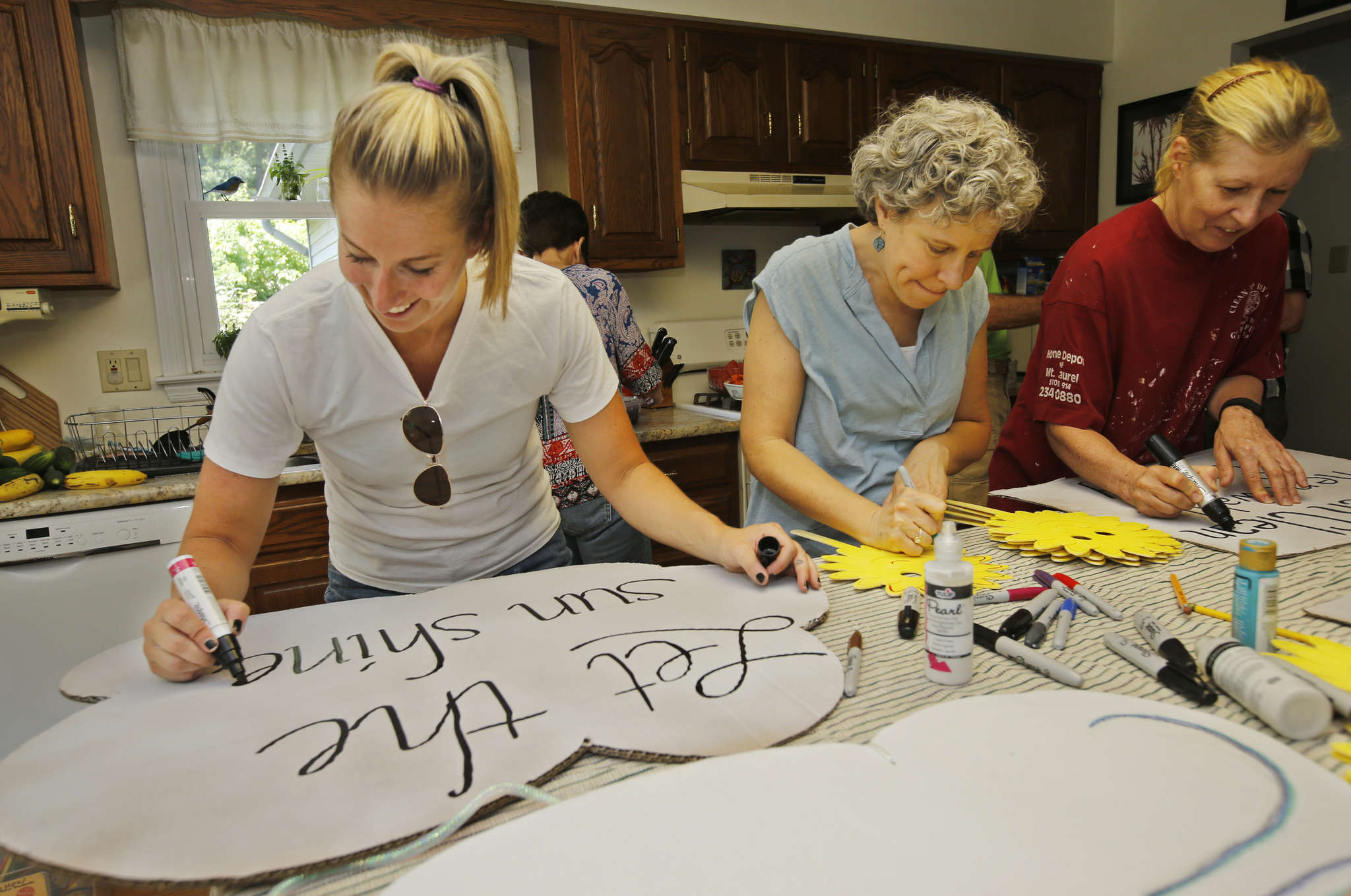 "Jessica Franzini (left), Caren Kaufman, and Arlene Anderson (right) design signs promoting alternative energy for the ""Clean Energy March"" on Sunday before the DNC. Franzini said they want leaders to implement ""innovative technologies that already exist."""