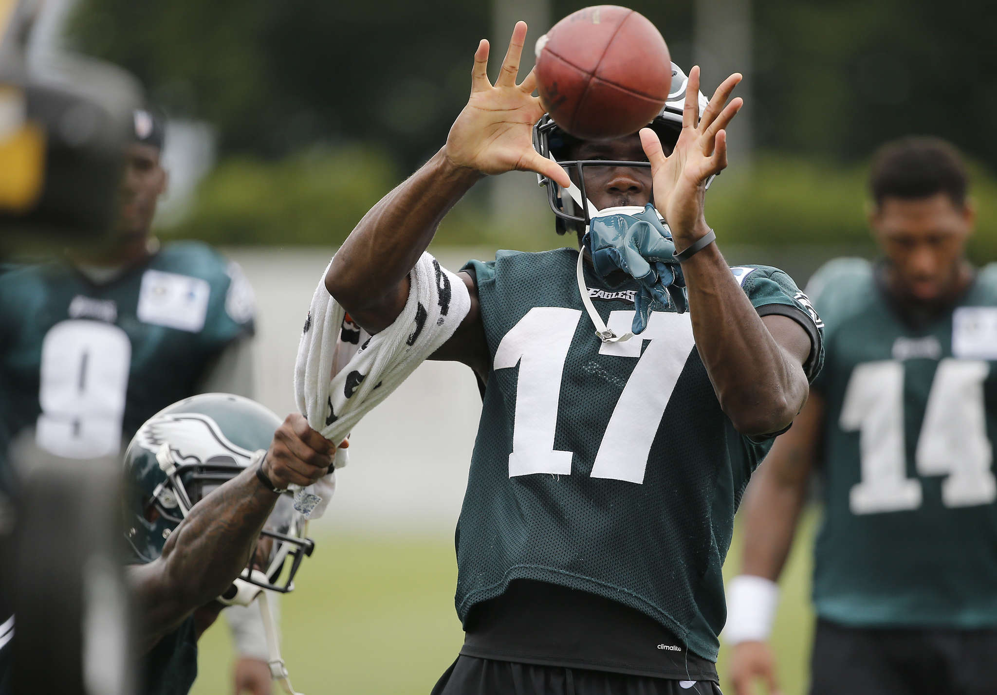 Josh Huff uses a towel to pull the arm of Nelson Agholor during a drill.