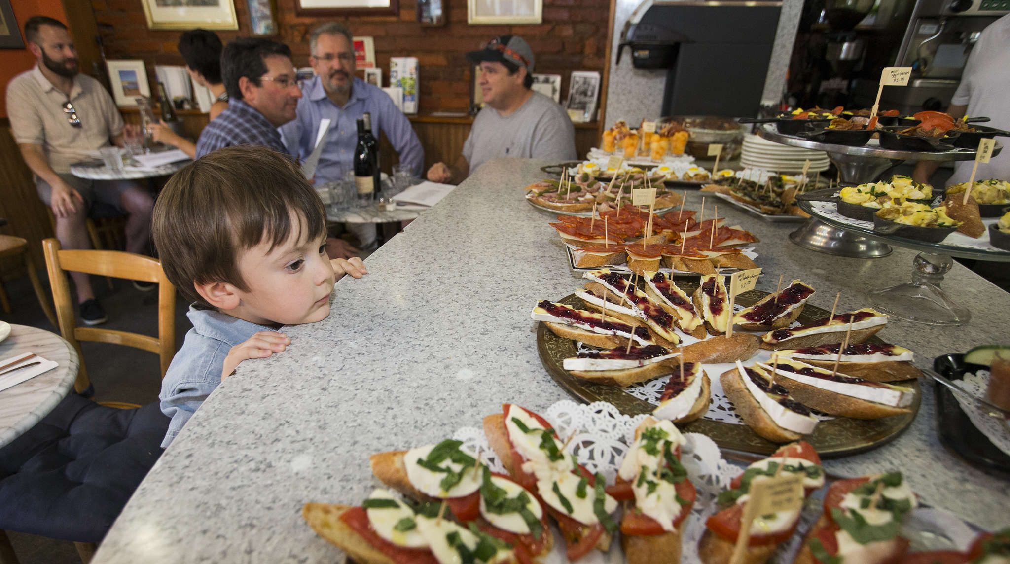 Café Lutecia, a longtime breakfast-lunch spot in Fitler Square, has begun serving Basque-French tapas dinners on Tuesdays only. Ogden Snow, 3, looks over the evening´s offerings of small plates of appetizers on the wraparound counter.
