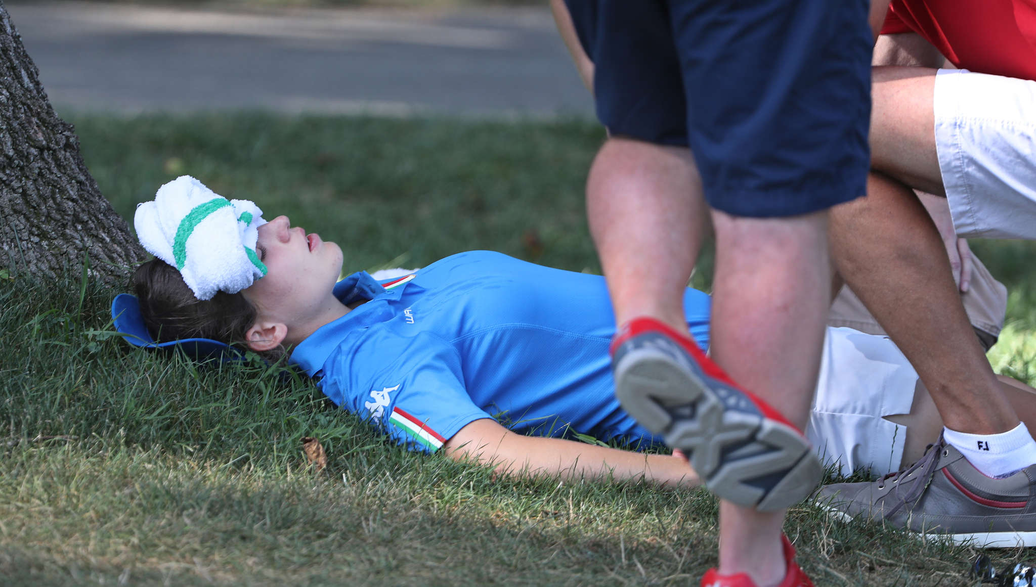 Virginia Elena Carta is overcome by heat and rests after the 13th hole. MICHAEL BRYANT /Staff Photographer
