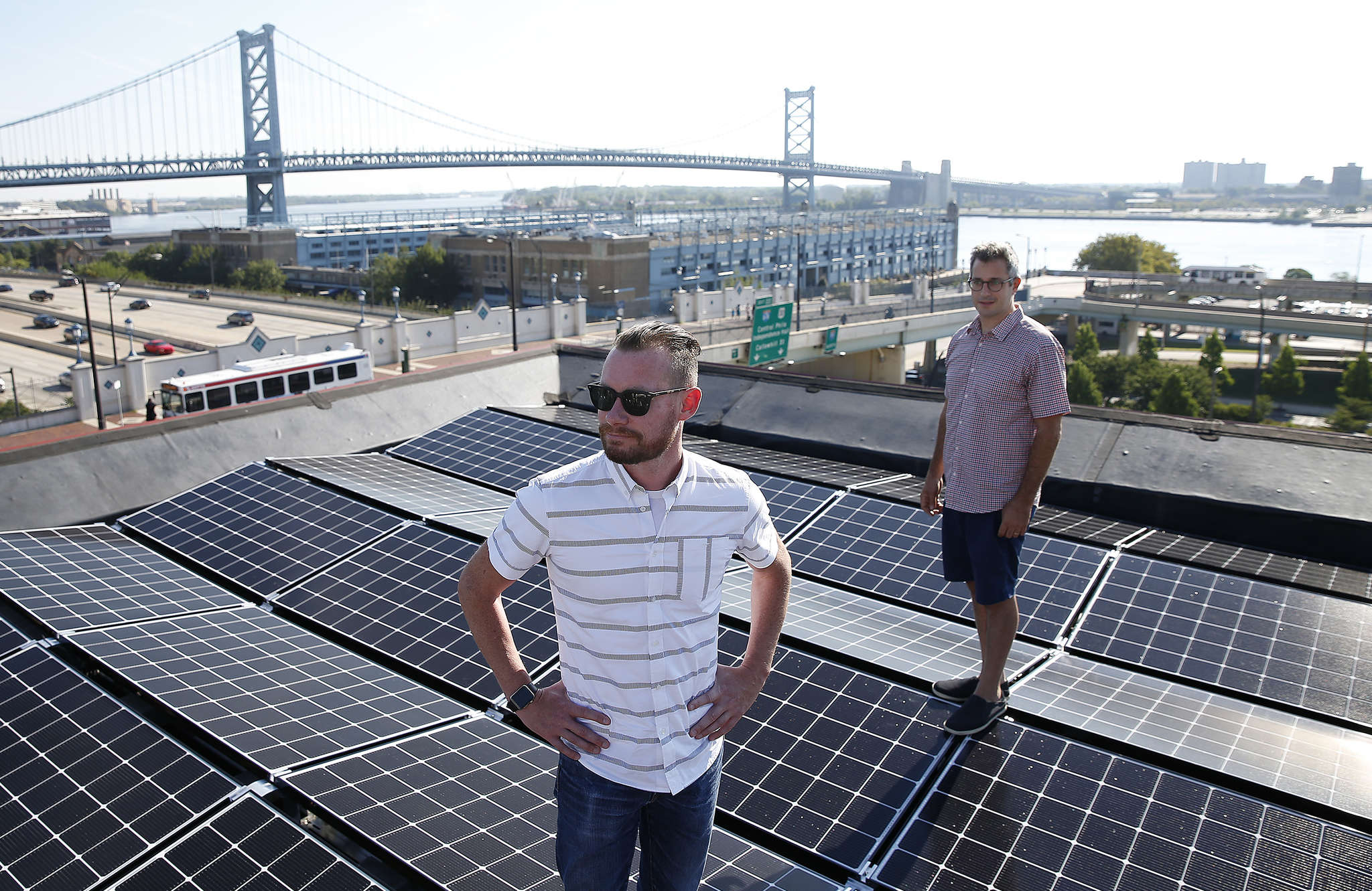 WebLinc cofounder and CEO Darren Hill (left) poses on his 38-panel solar roof with Micah Gold-Markel, founder of Solar States in Philadelphia.