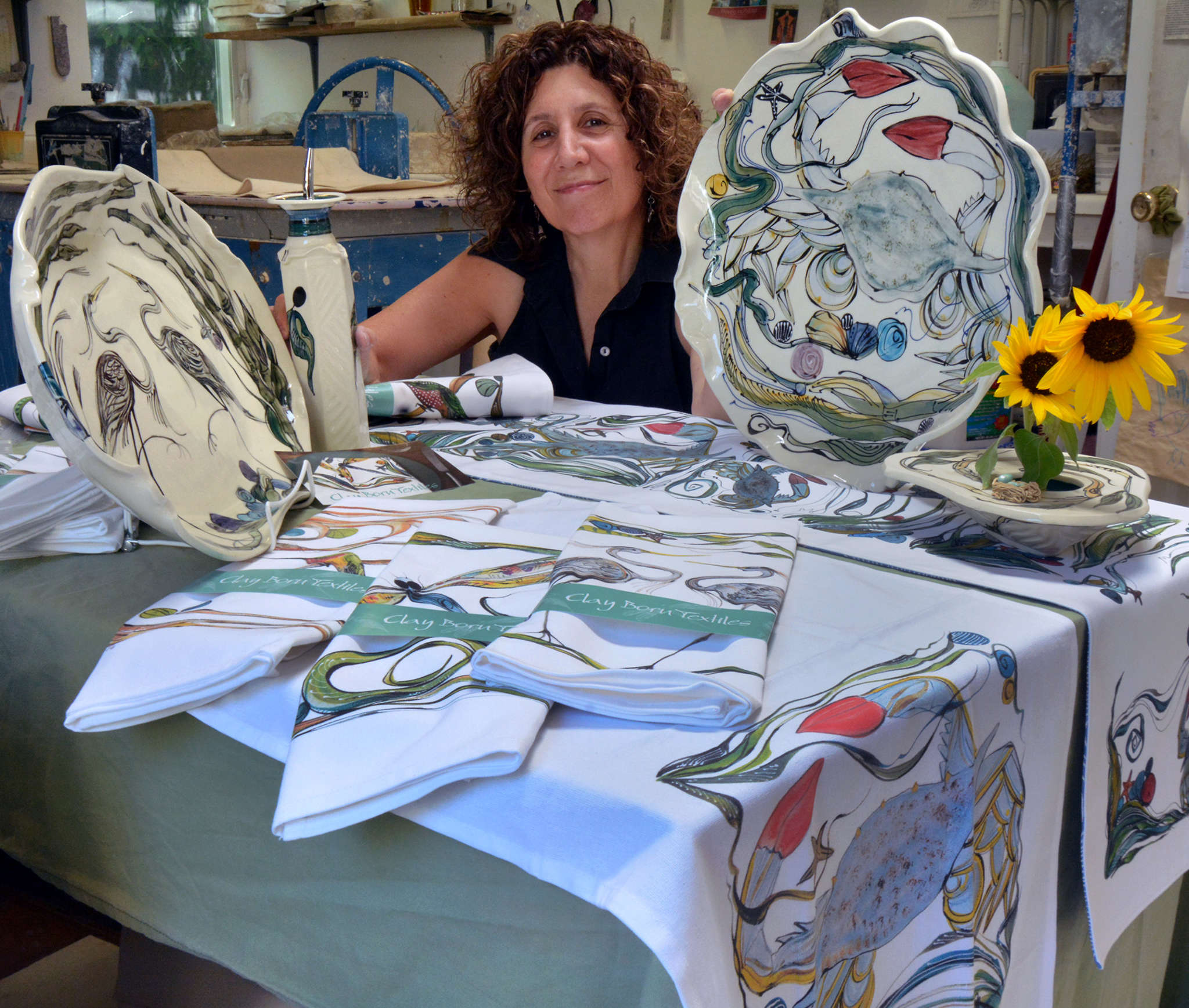 Artist Nancy Salamon at her Clay Born studio in West Chester with some of her hand-painted ceramics and the new line of coordinating textiles digitally printed with her designs.