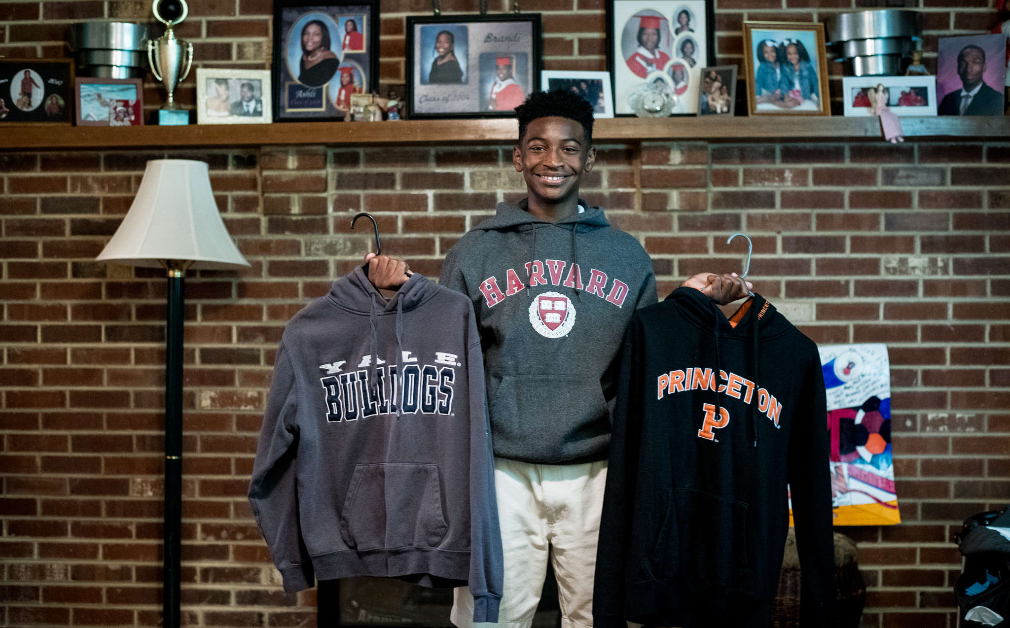 Calvin R. Bell III wears a Harvard sweatshirt while holding others from Yale and Princeton. His goal is Harvard but he wants to be in the Ivy League in any case.