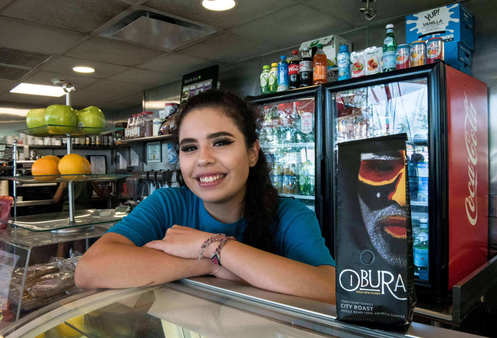 Isabella Bacciarini, a junior at String Theory High School and an employee at Logan Square Cafe in Center City, next to a bag of Obura brand coffee beans at the cafe.