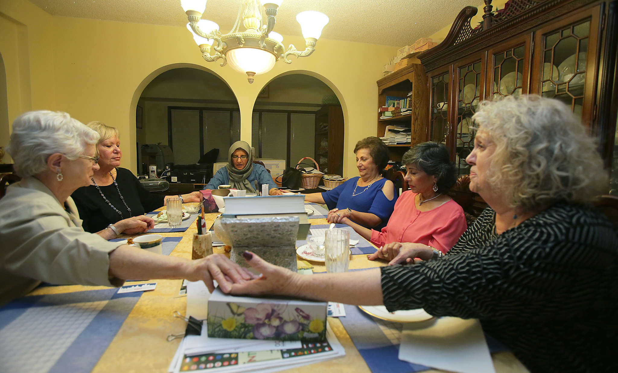 The Soul Sisters pray at the start of a meeting. The group began meeting in September 2011. The six members are (from left) Jane Kopas, who is Catholic; Pat Sandrow, who is Catholic; Zahida Rahman, who is Muslim; Harriet Schulman, who is Jewish; Farhat Biviji, who is Muslim; and Charlene Fenster, who is Jewish.