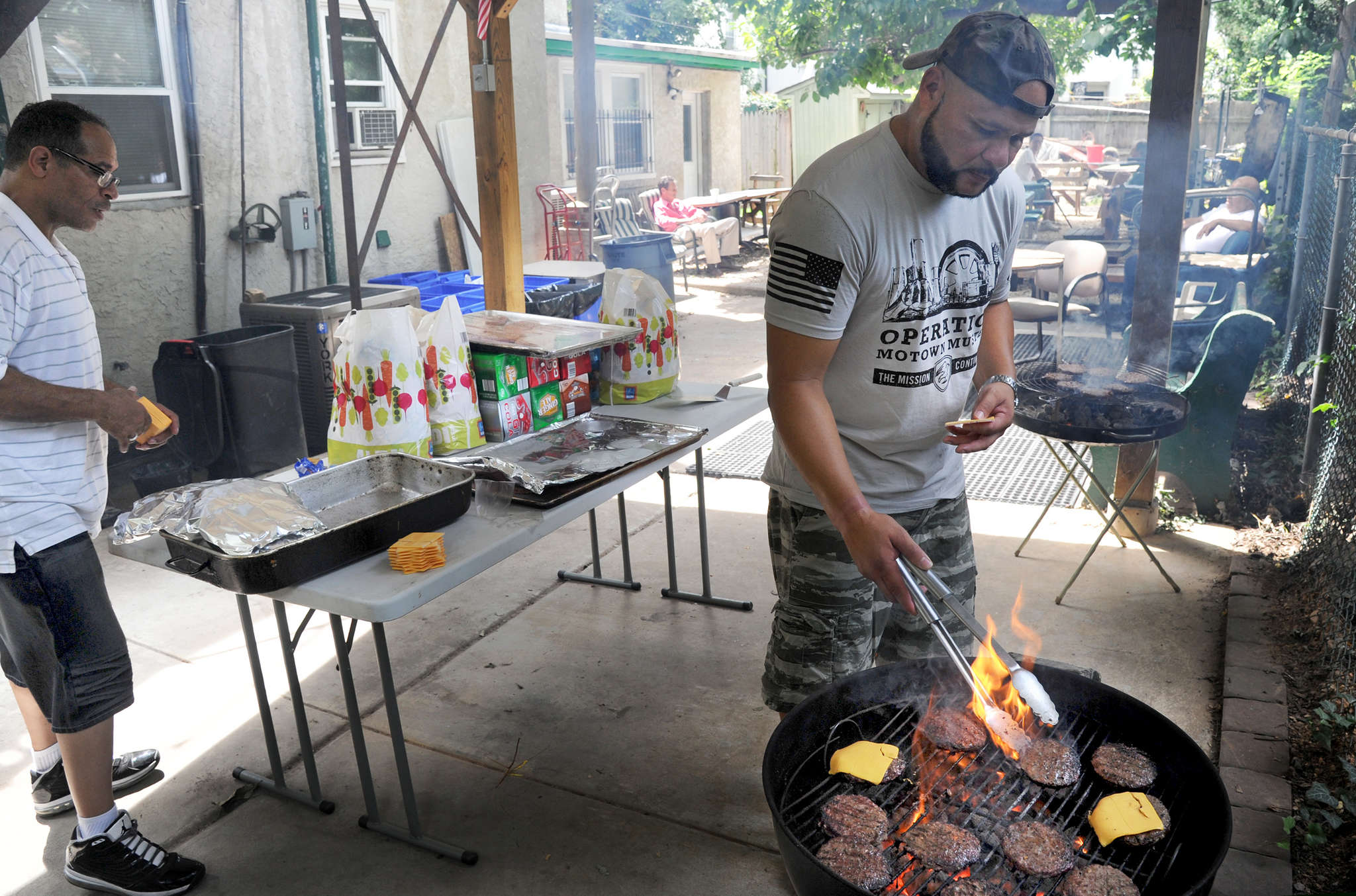 Jose Martinez, executive director of the Veterans Group, grills burgers at a facility for homeless vets in Powelton Village. He also works for a nonprofit that organizes community projects.