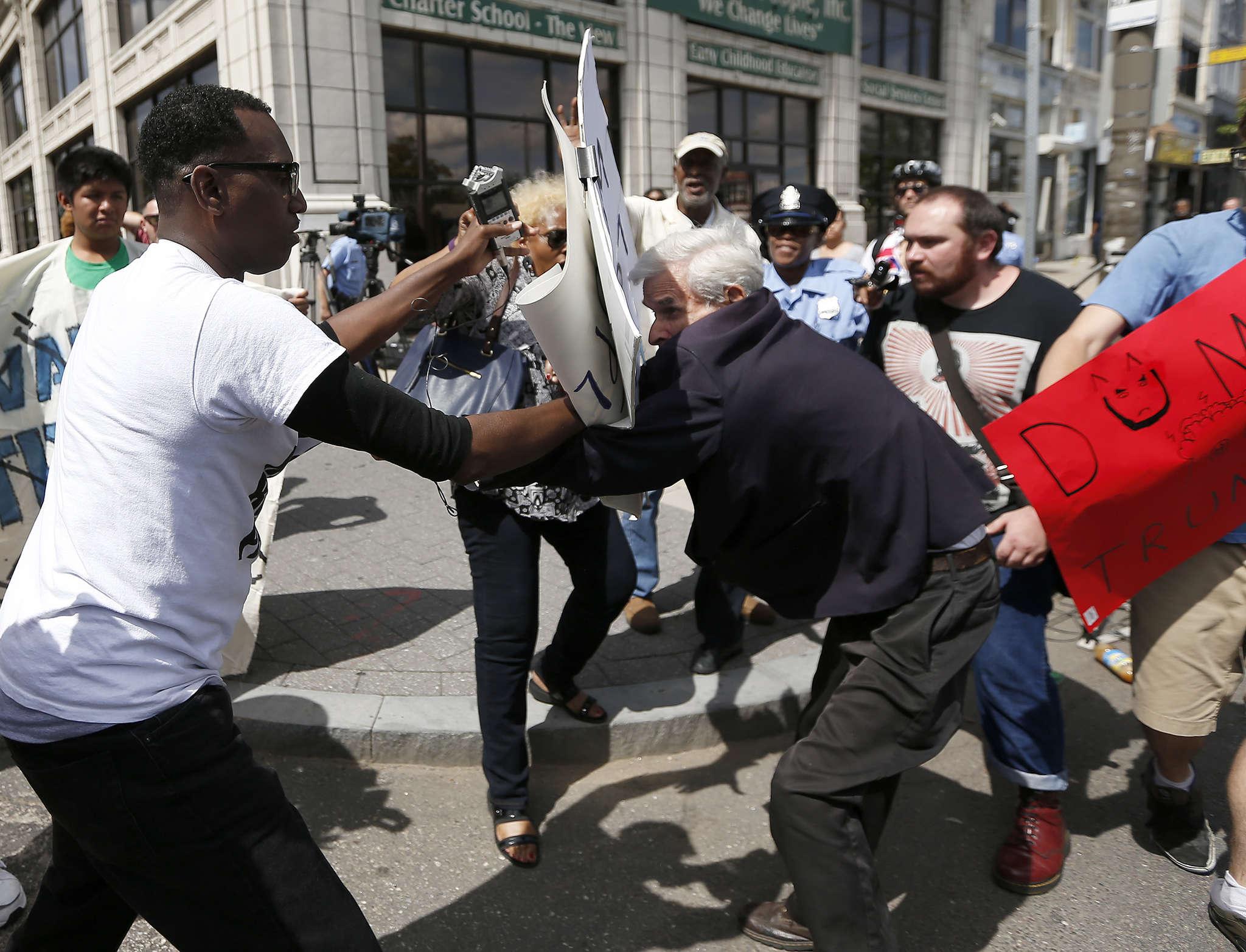 Protester Asa Khalif (left) and Donald Trump supporter Jerry Lambert scuffling Friday in Philadelphia.