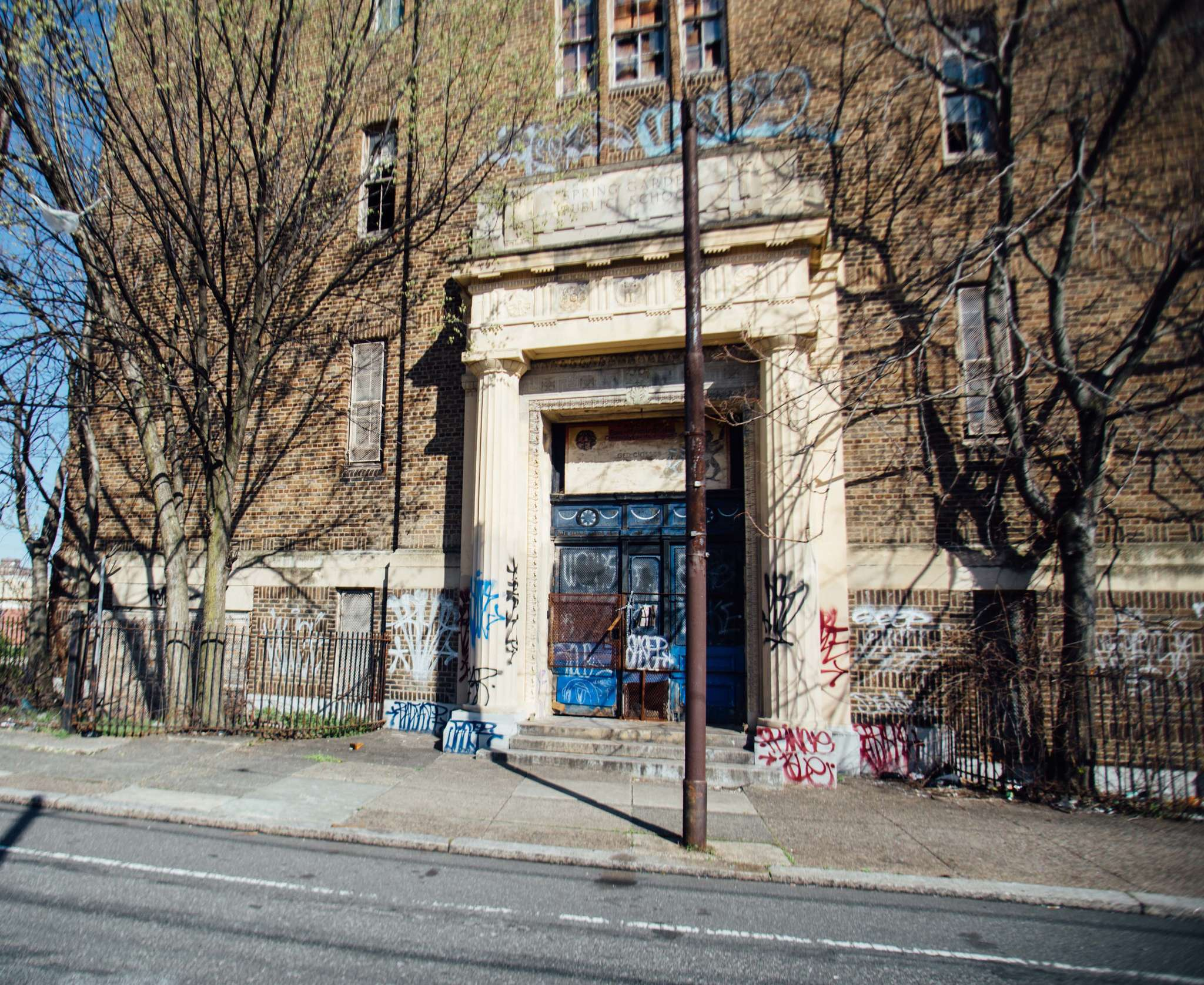 The front of the former Spring Garden School on 12th Street in Philadelphia. The 1920s three-story brick building features a limestone entrance surround and parapet as well as decorative tile. The school has been out of service for most of the last 40 years.