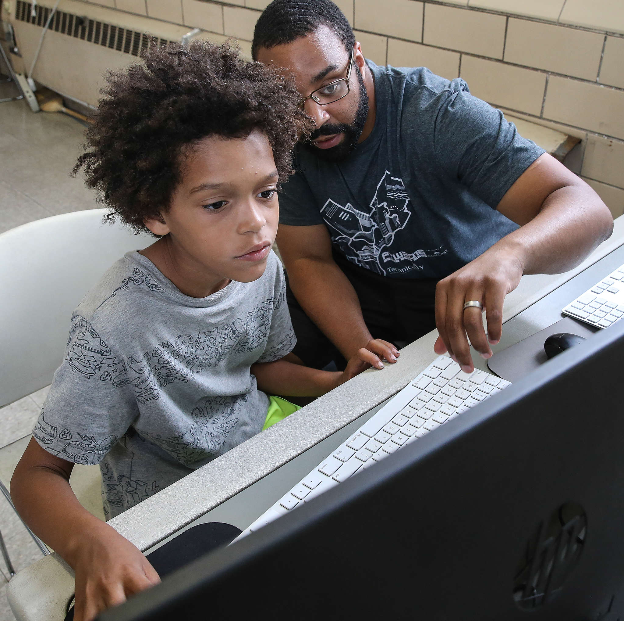 Sylvester Mobley works with Marlowe Whittenberg , 8, at a Coded by Kids workshop at the Marian Anderson Recreation Center. Coded by Kids is a nonprofit offering technology classes at city recreation centers for young people age 5 to 18. STEVEN M. FALK / Staff Photographer