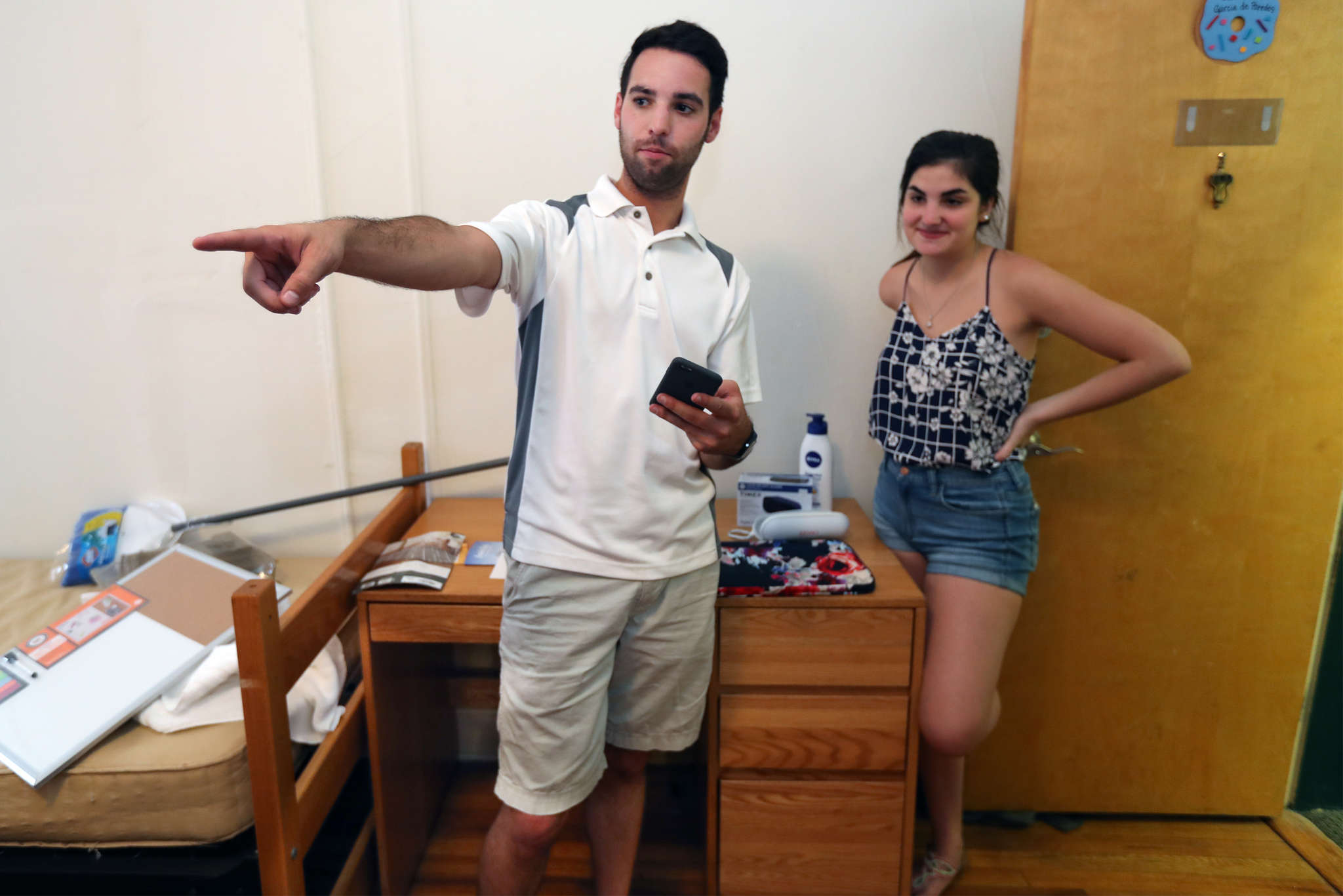 Brett Barry goes over the belongings that he and his brother Sean brought up for Isabela Garcia, from Panama, at an apartment at St. Joseph´s University. The Barry brothers do the sweating so that students don´t have to.