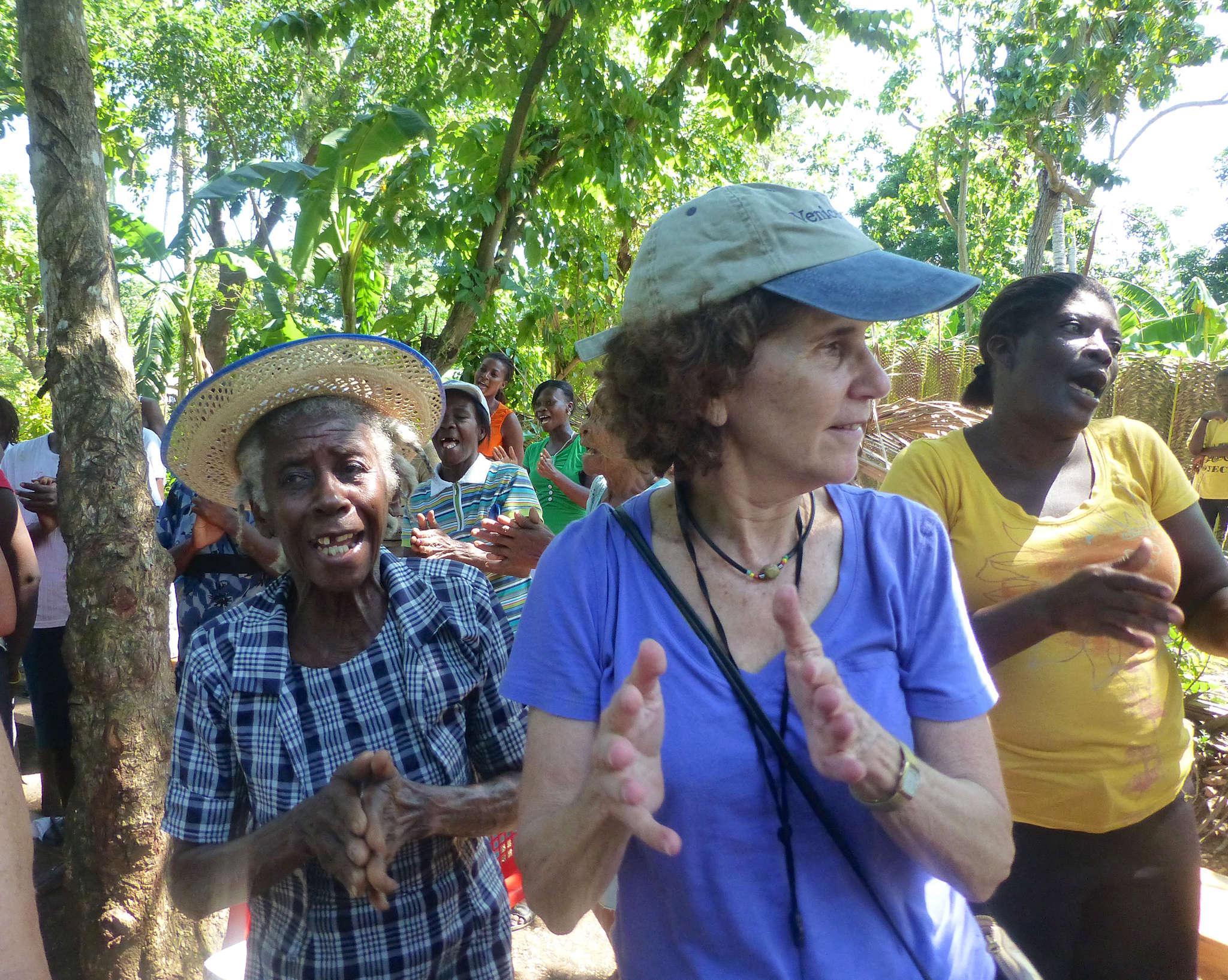 WIL co-founder Linda Resnick (center) sings and dances at a meeting for the micro-finance institute Fonkoze in Haiti. WIL provides loans and services for women in developing regions.