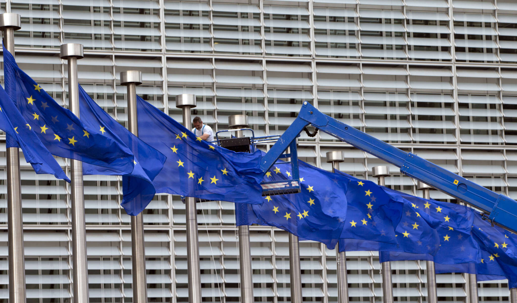 A worker makes flag adjustments at EU headquarters in Brussels. The Brexit vote has caused complications for firms.