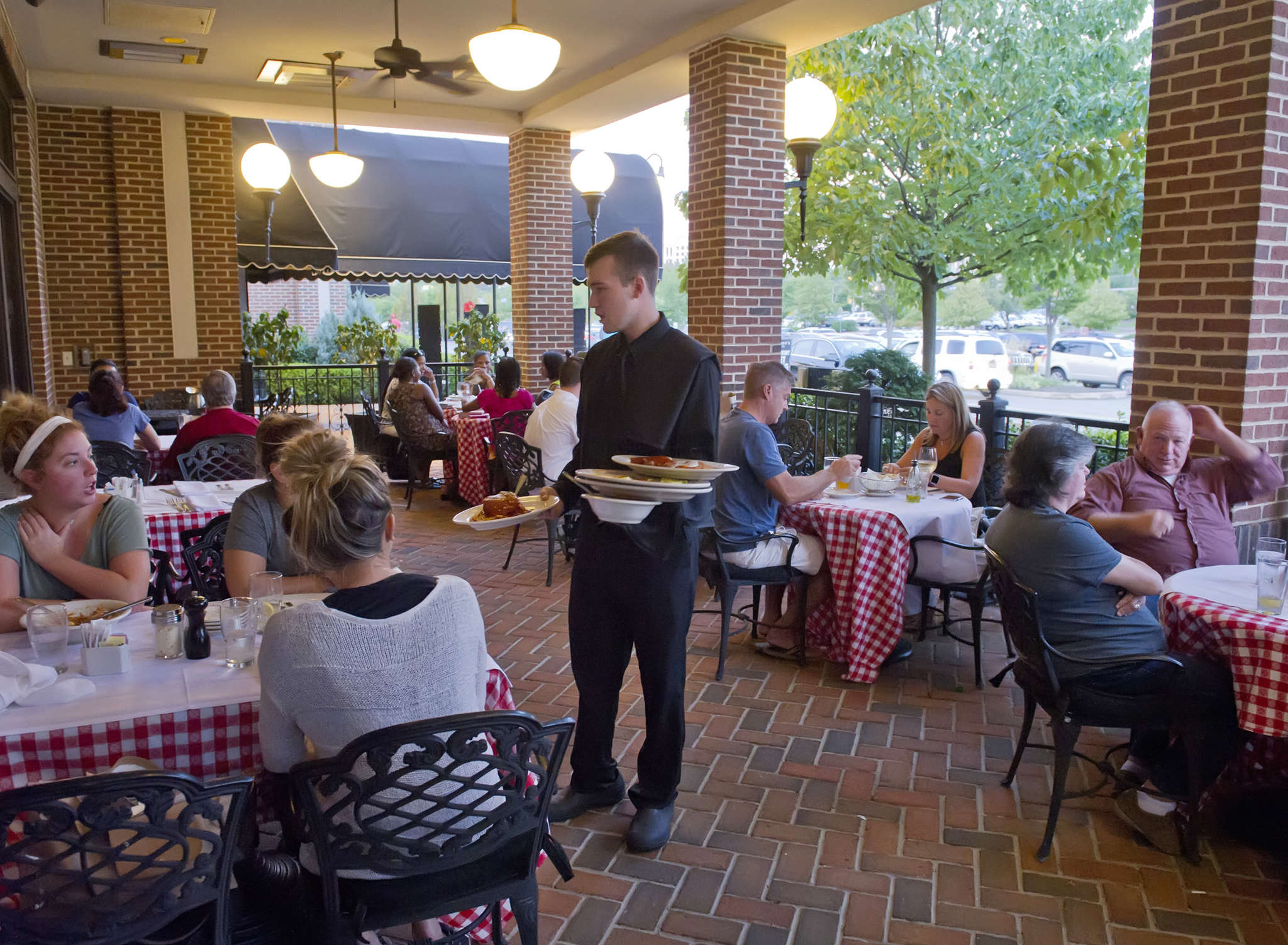 Waiter Ryan Eckel (left) serves customers on the patio of Maggiano´s Little Italy at the Cherry Hill Mall.