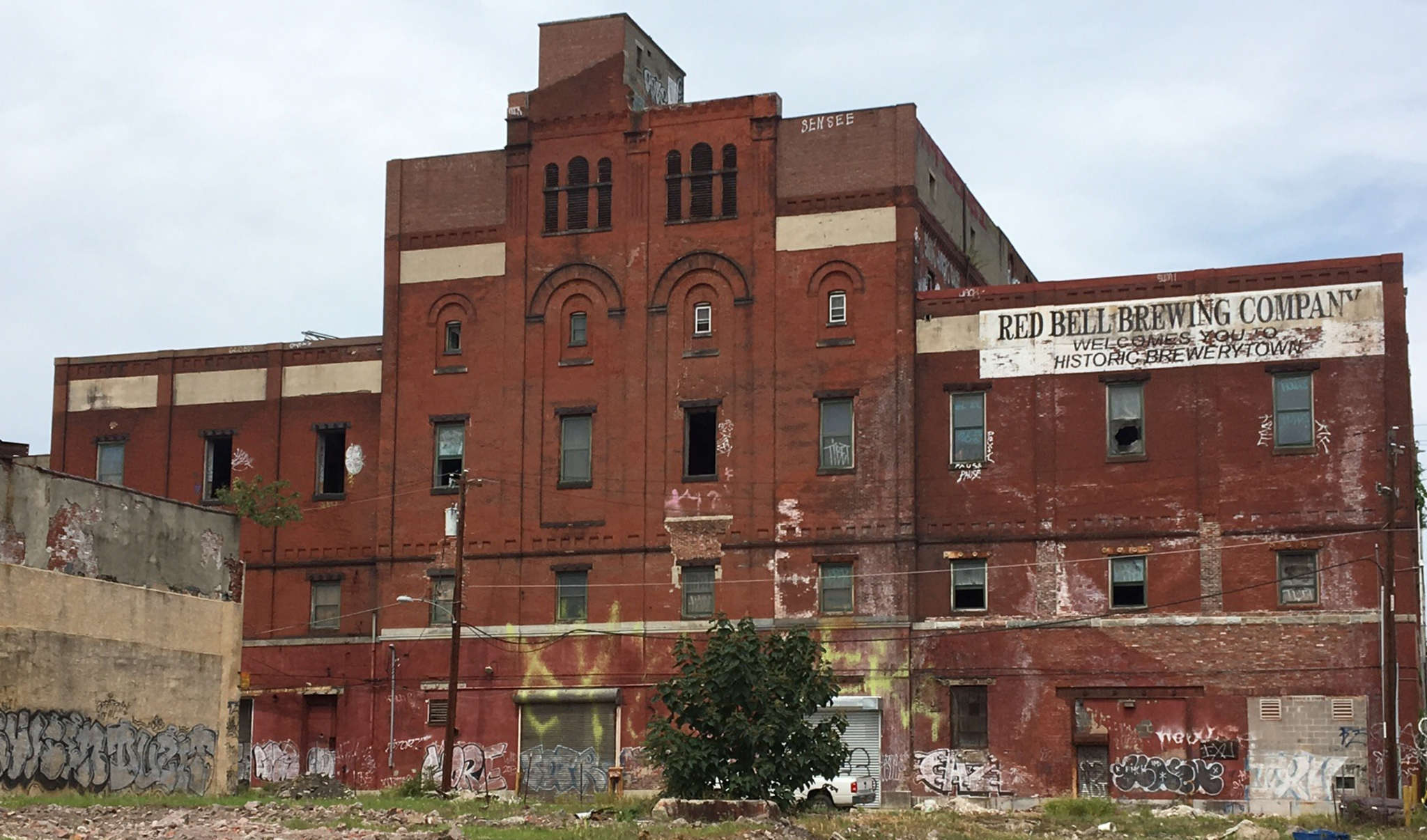 The former brewery, with its five-story central hall, three-story wings, and arched windows that draw the eye upward, has recently been sold to a developer.