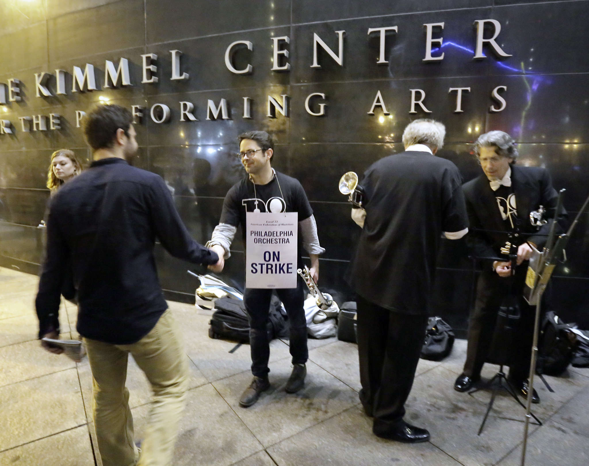 Philadelphia Orchestra members are thanked after playing briefly outside the Kimmel Center while others walked the picket line Friday evening.