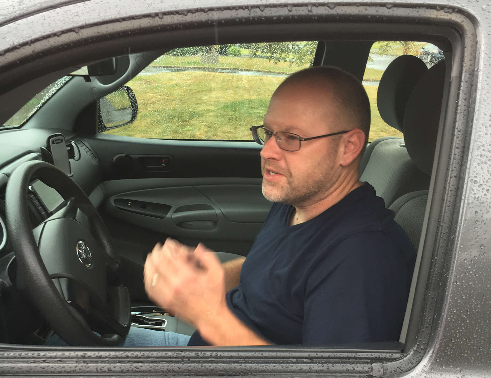 Shawn Gill at the wheel of his 2014 Toyota Tacoma that he drove for Lyft and Uber, until his license was suspended as a result of identity theft.