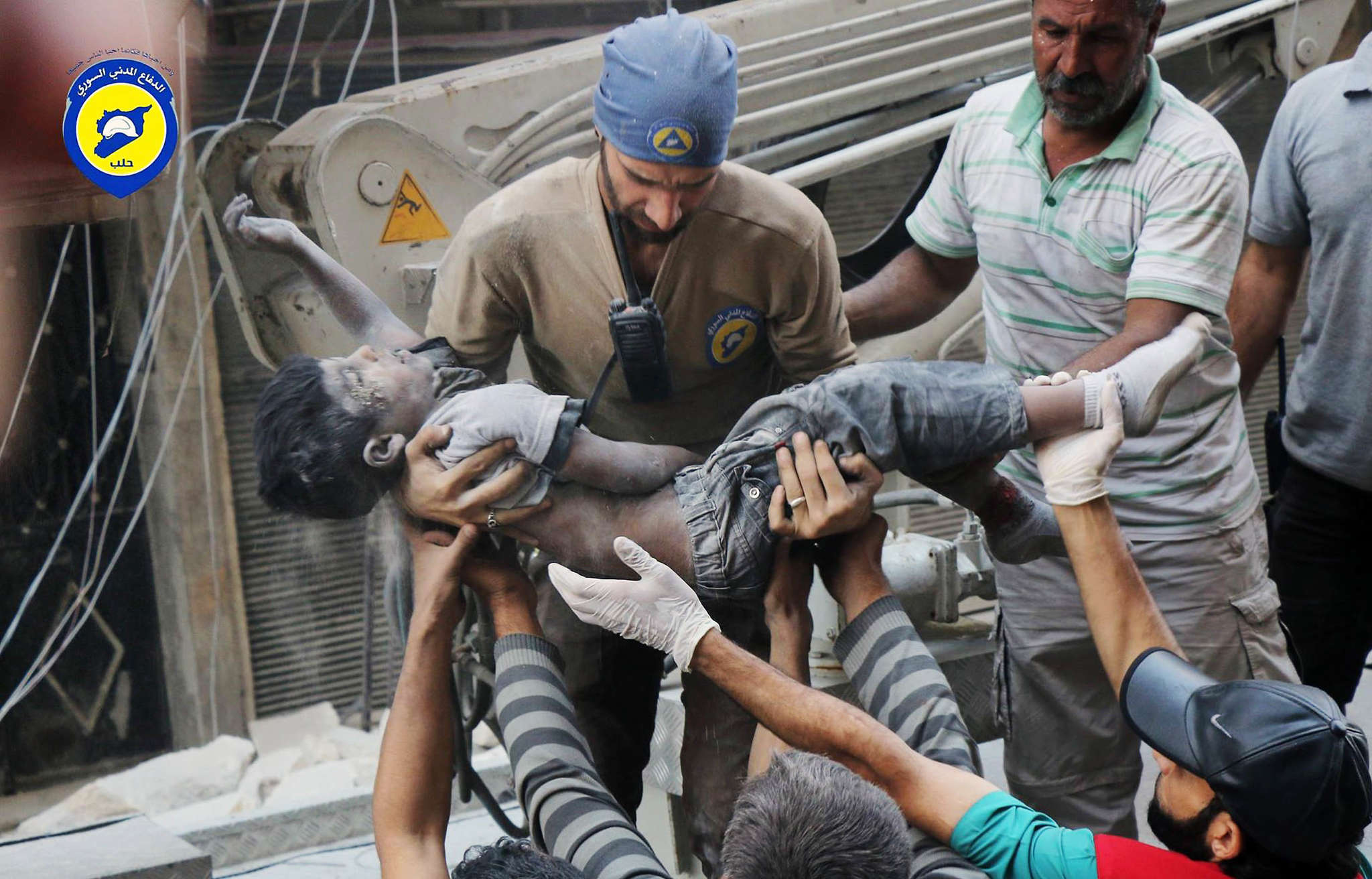 Syrian volunteers, the White Helmets, carry the body of a child after another round of devastating airstrikes in Aleppo.