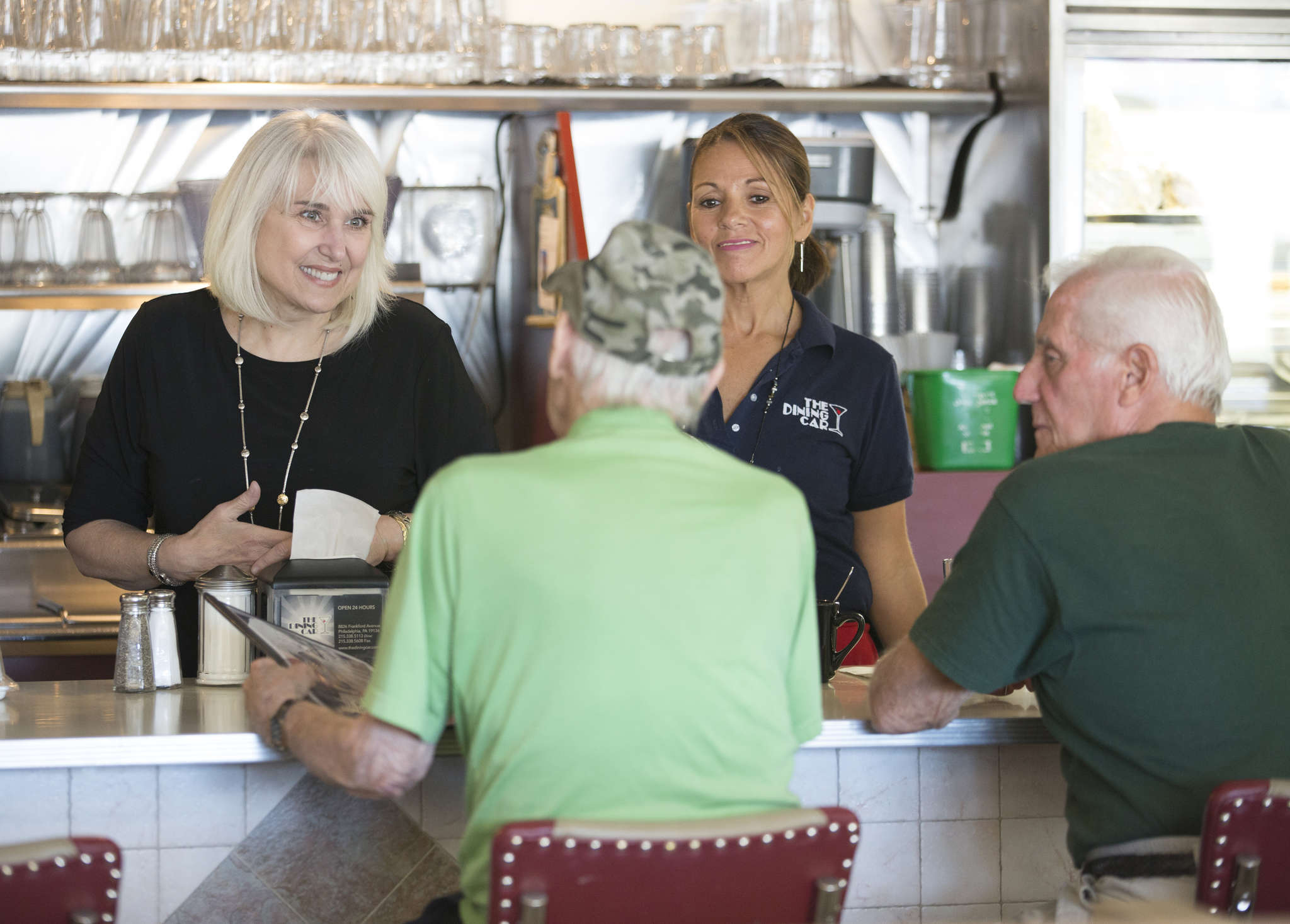 Nancy Morozin (left), owner of the Dining Car diner on Frankford Avenue, and Jackie Mercado talk with customers there.