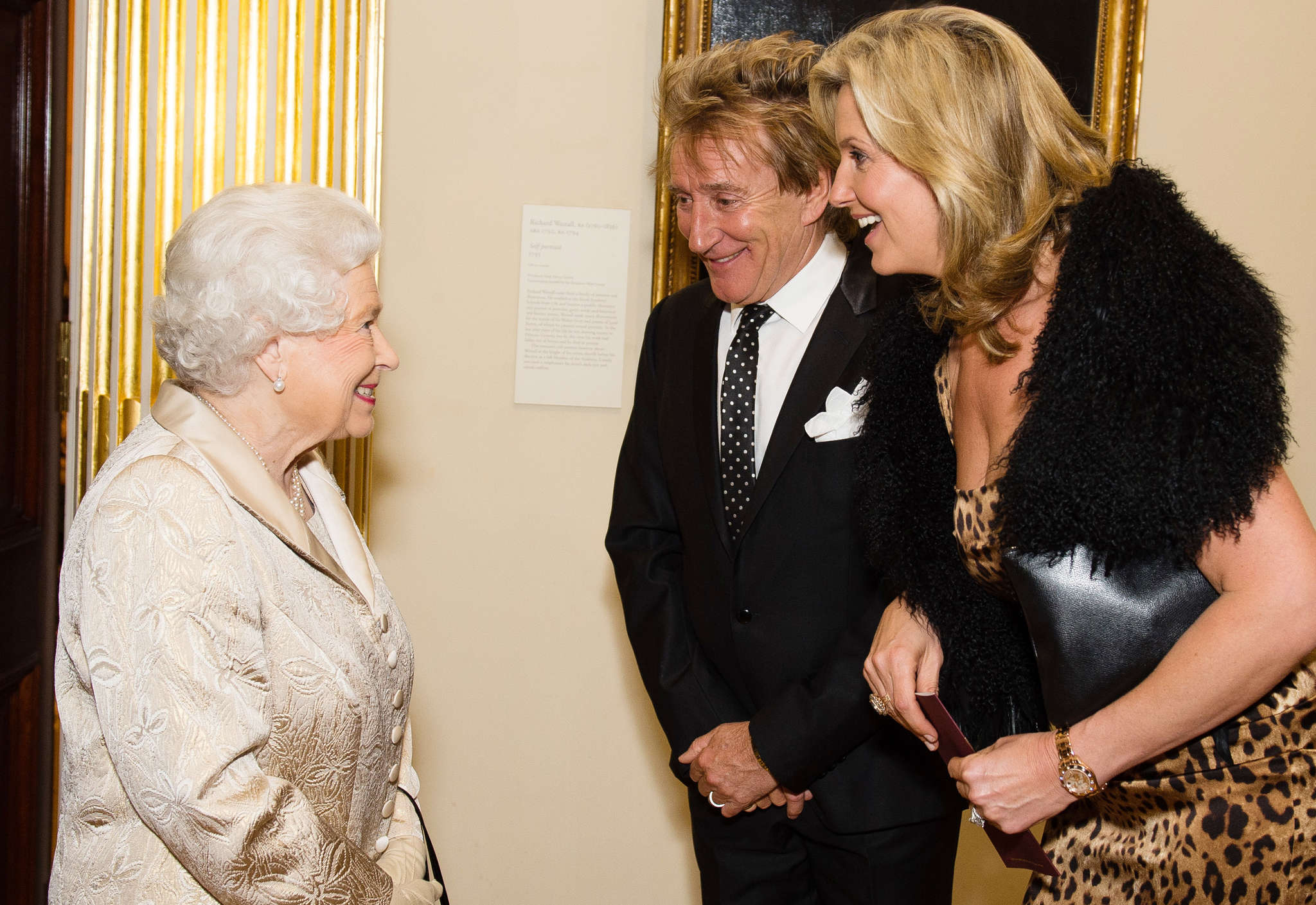 Queen Elizabeth II greets Sir Rod Stewart and wife Penny Lancaster after he was awarded a knighthood.