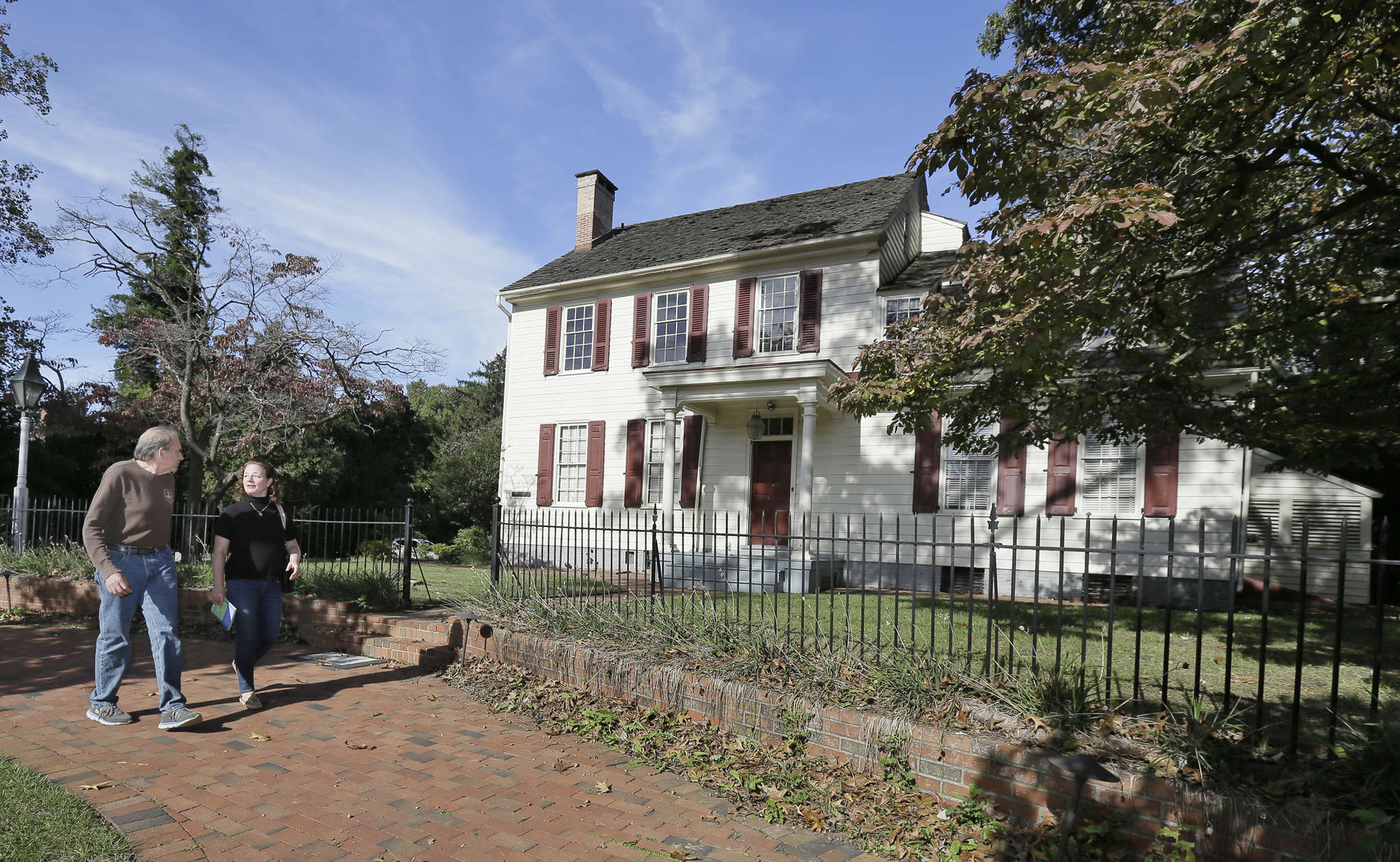 """Preservationists Brian Kelly and Kim Custer pass the historical Boxwood Hall in Haddonfield. Under a preliminary proposal, """"Boxwood Arts,"""" with galleries and a 300-seat theater, would be built behind it."""