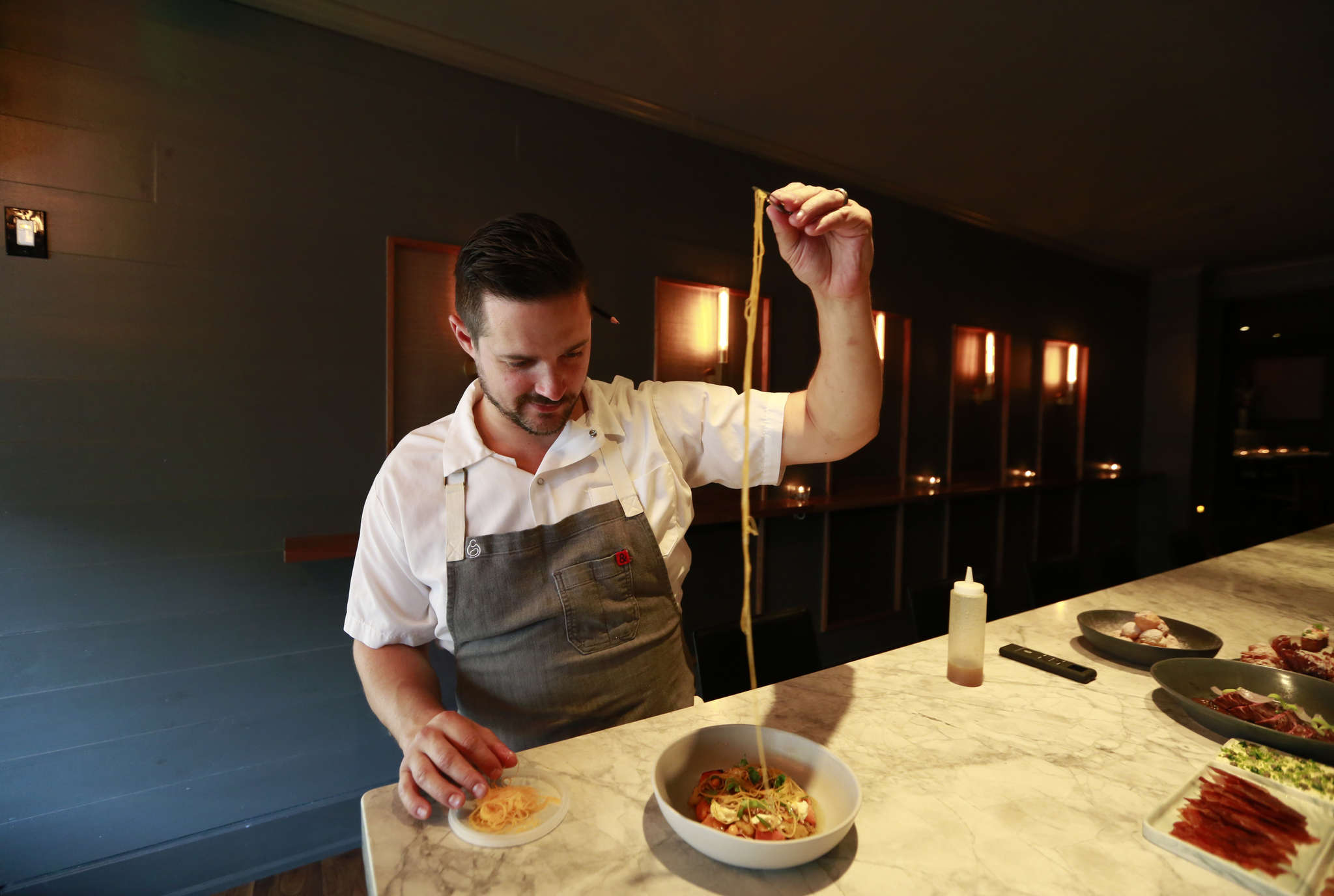 Chef-owner Nicholas Elmi completes the squash salad, which has chunks of grilled kuri and delicata squash tumbled with snappy noodles spiralized from a butternut, at ITV.