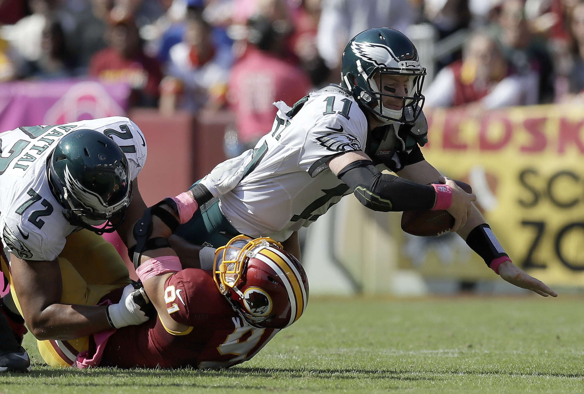 Carson Wentz is sacked by Ryan Kerrigan, who has beaten right tackle Halapoulivaati Vaitai. YONG KIM/Staff Photographer