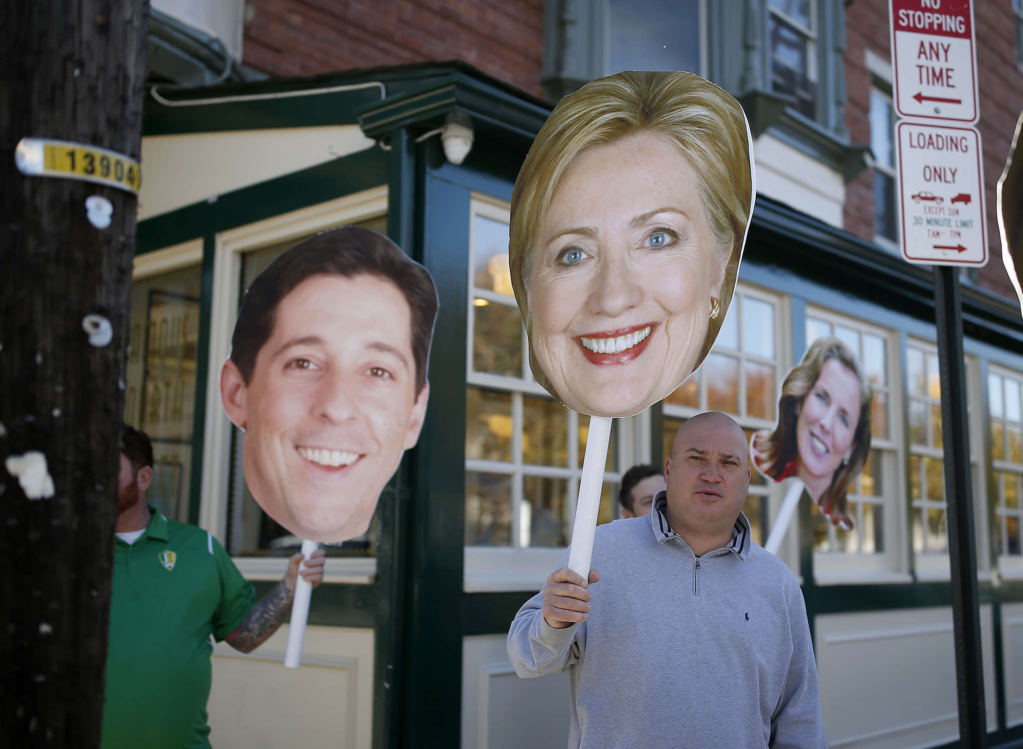 IBEW 98 member Eric Dwornik holds up a large photo of Hillary Clinton at Famous 4th Street Deli.