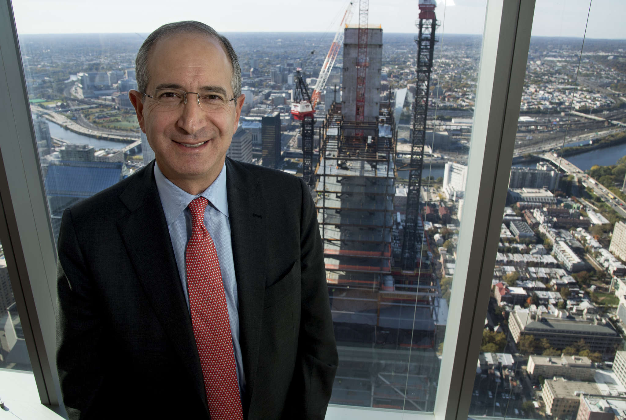 Brian L. Roberts, Comcast CEO, at the Comcast Center, whose second tower is under construction behind him.