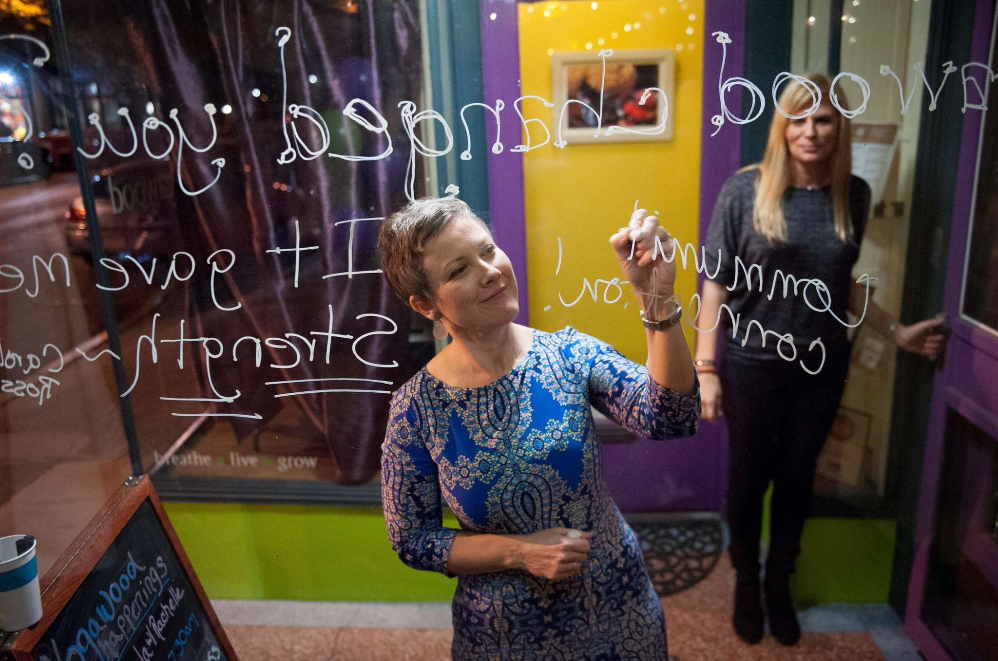 Yogawood owner Beth Filla writes on the studio´s window about what the discipline has given her during a party to celebrate Yogawood´s 10th anniversary. She considered canceling after the election last week.