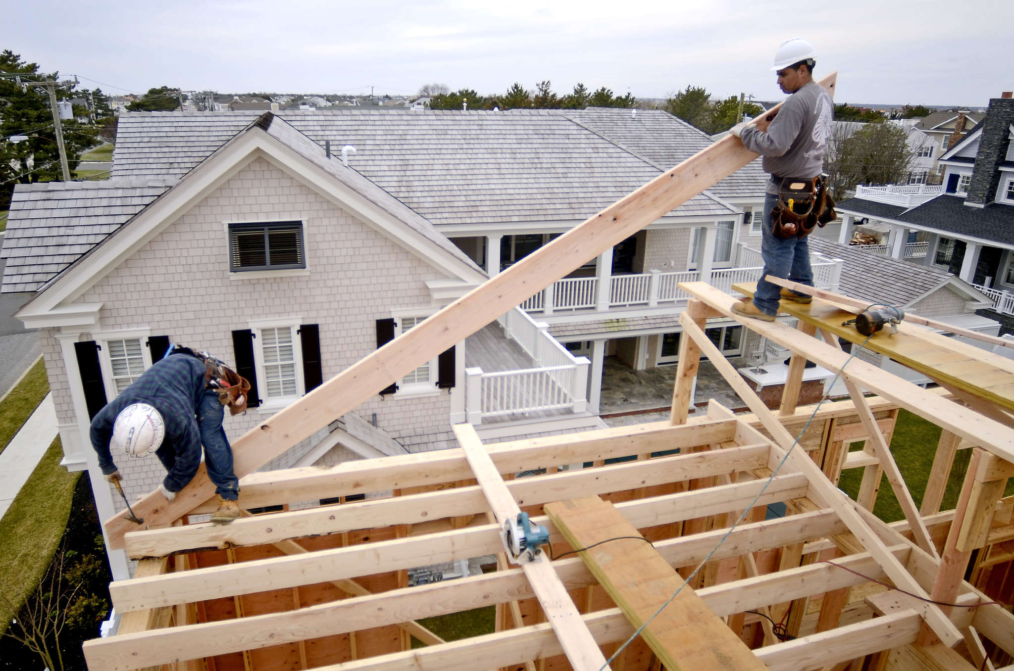 Workers help build a home in Stone Harbor. Construction workers are in short supply and competition is mounting among builders in 33 major markets as the number of new-home communities increases.