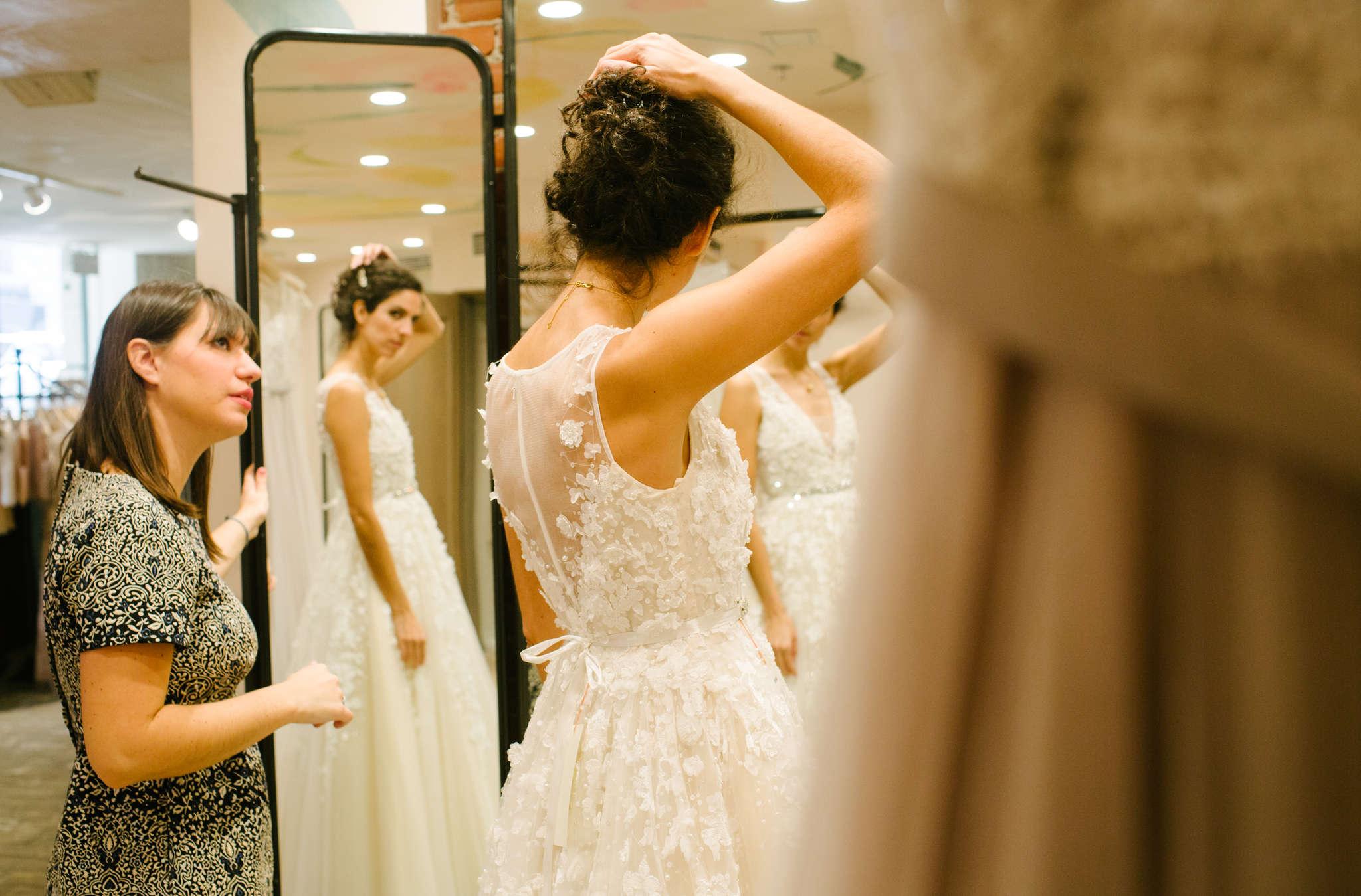 Stylist Beth Rosella helps Ignacia Behncke try on a wedding dress in a new BHLDN location inside a Center City Anthropologie store.