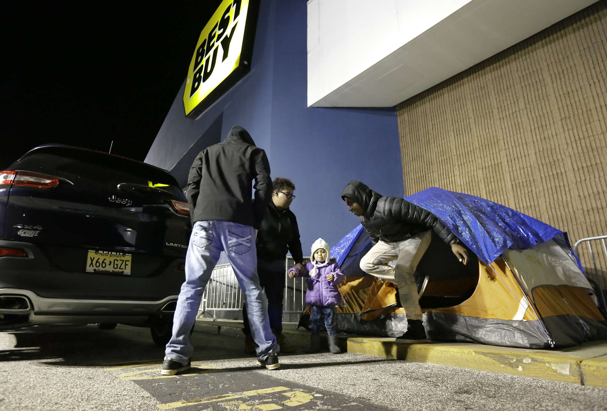 <br />At the Best Buy in Deptford, Sumara Rembert (second from left) gets help from nephews Ashton (left) and Jordan Pendleton, with niece Legend Pendleton, 2, setting up a tent to keep a good place in line for the Black Friday opening.<br />