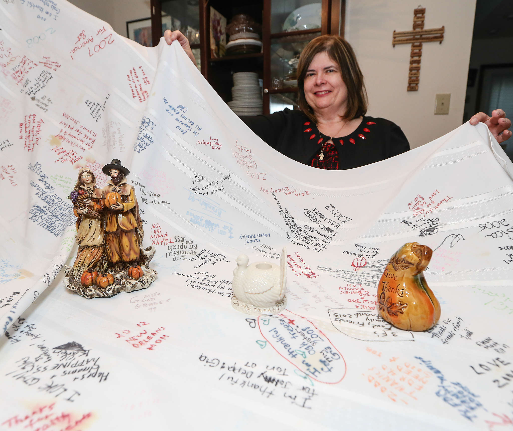 Pat Quigley shows a previous polyester tablecloth with notes from family members gathered for the holidays. Other families have similar traditions, though it is difficult to determine the source of the idea.