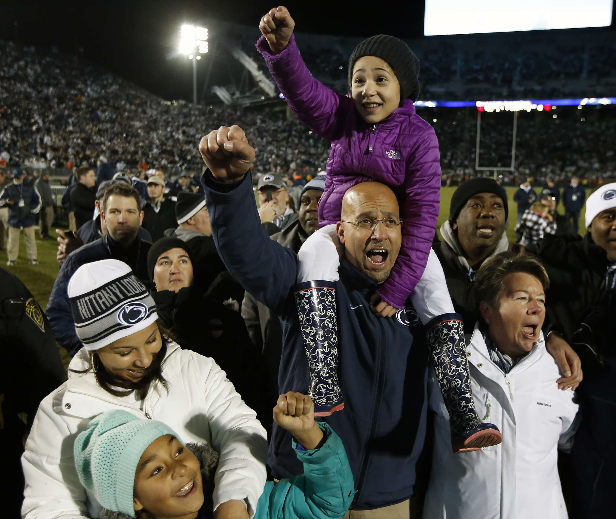 Penn State coach James Franklin carries his daughter Addy Franklin on his shoulders while his wife Fumi Franklin (left) celebrates with daughter Shola Franklin.