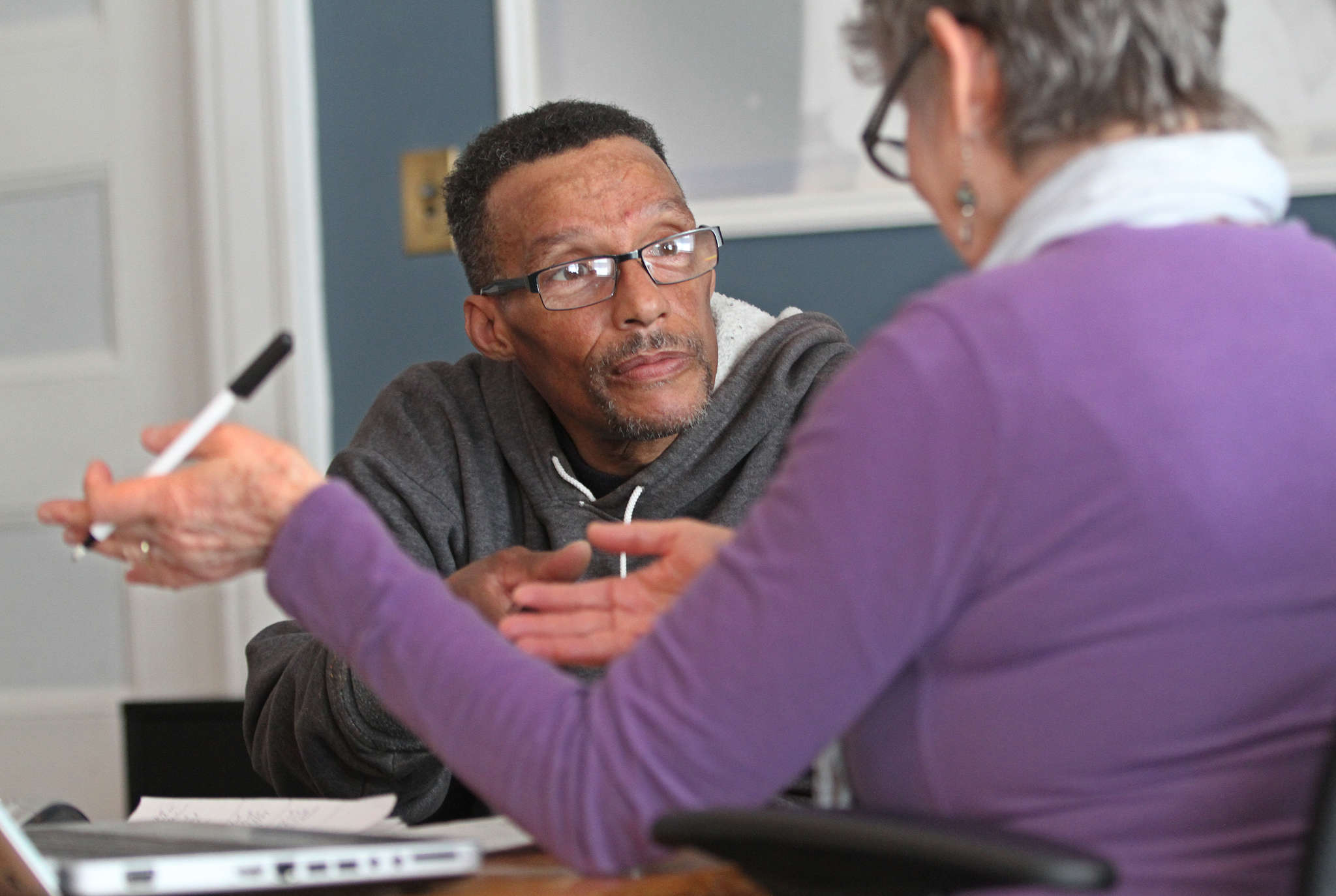 Applicant Lloyd Brown listens to Barbara Bloomfield, a certified application counselor, at St. Elizabeth´s Wellness Center.