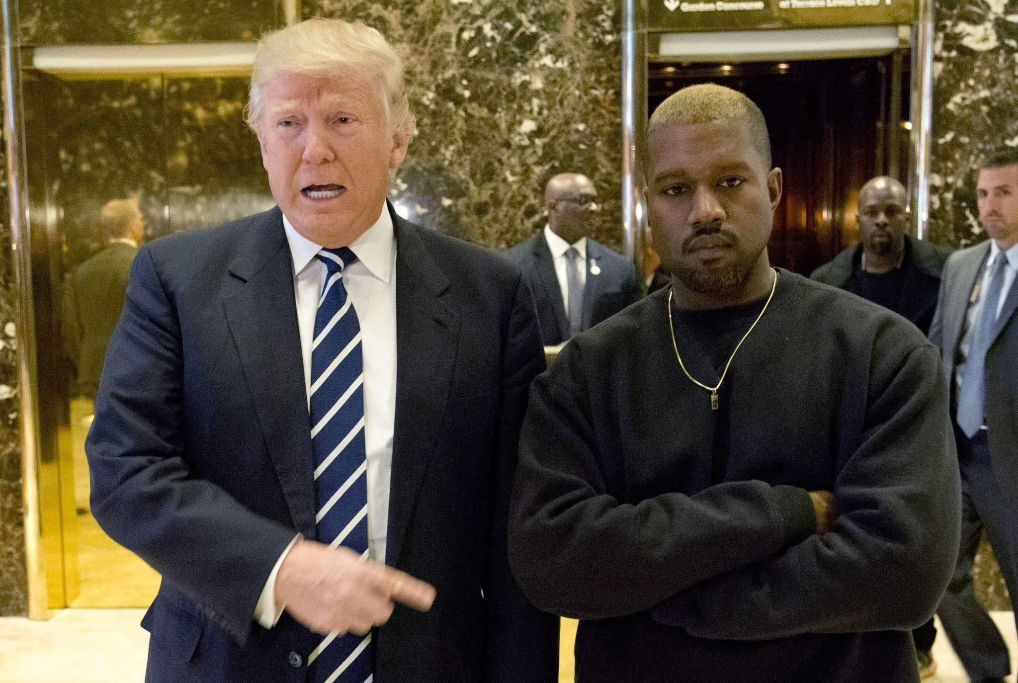 "President-elect Donald Trump poses with rapper Kanye West for a picture in the lobby of Trump Tower in New York. It wasn´t immediately clear what they discussed Tuesday morning. ""We´ve been friends for a long time,"" Trump told reporters. West only smiled when asked about the possibility of performing at Trump´s inauguration."