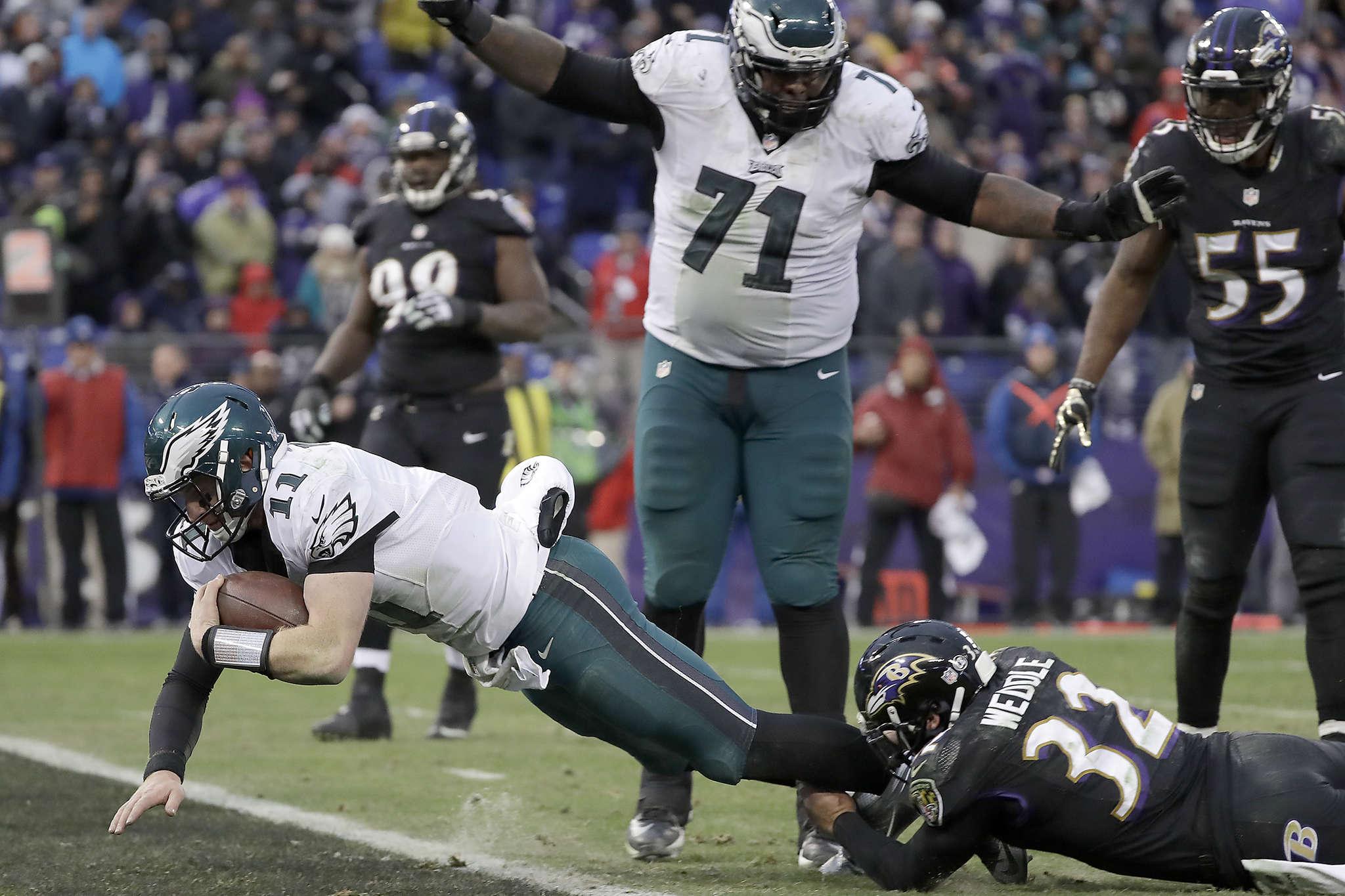 Carson Wentz runs through Baltimore´s Eric Weddle for late-game touchdown. YONG KIM/Staff Photographer